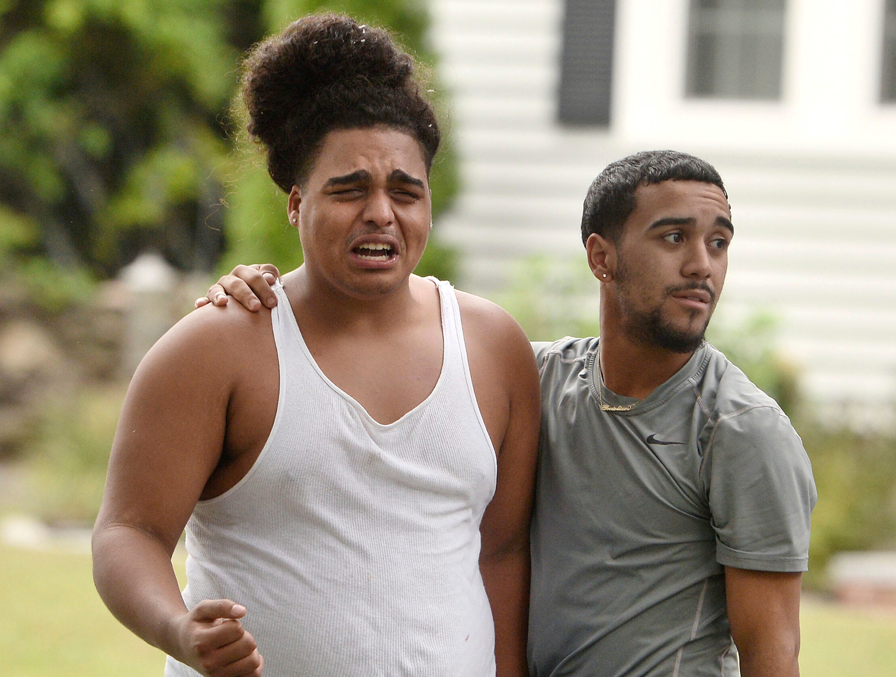 Two young men comfort each other, Thursday, after a gas explosion destroyed a house on Chickering Street killing a teenager who was in his car in Lawrence, Mass.