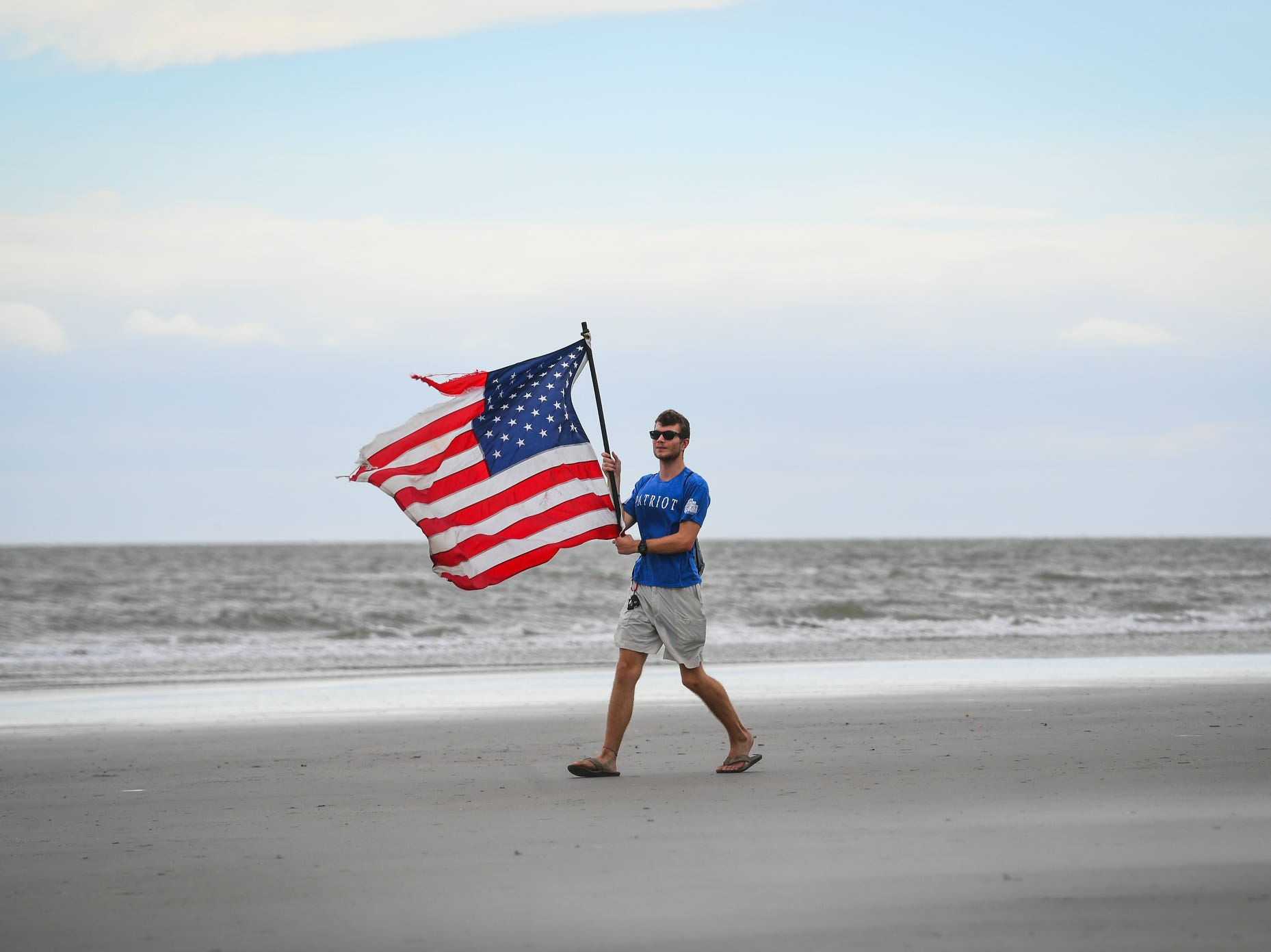 Mason Moise, 18, from Charleston, S.C.,  carries a U.S. flag in the increasing winds on Isle of Palms Beach Friday afternoon prior to the arrival of Hurricane Florence.