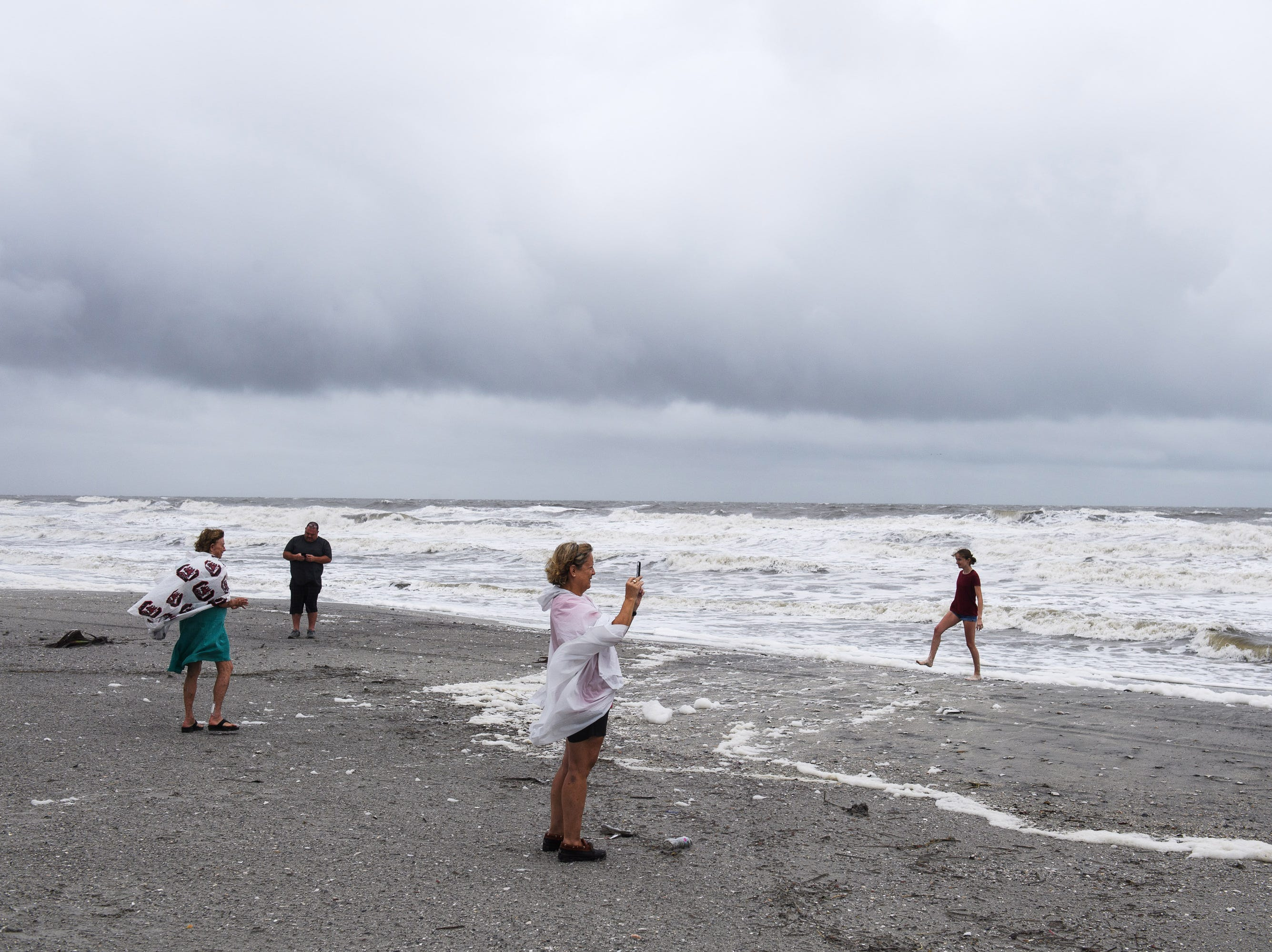 North Myrtle Beach, S.C. residents check out the beach as high tide begins to come in on Saturday, Sept. 15, 2018.