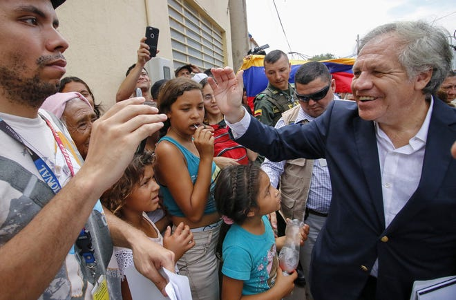 """The Secretary-General of the Organization of American States (OAS), Uruguayan Luis Almagro (R), greets Venezuelans during his visit to the Divina Providencia migrant shelter in Cucuta, Colombia, on the border with Venezuela, on September 14, 2018. - Almagro is in Cucuta as part of a three-day visit to Colombia to discuss the Venezuelan migratory crisis which has been described as """"the largest migration crisis"""" of the Western Hemisphere. According to the United Nations, about 2.3 million people left the oil-producing country since 2014, plunged into an acute economic crisis. (Photo by SCHNEYDER MENDOZA / AFP)SCHNEYDER MENDOZA/AFP/Getty Images ORIG FILE ID: AFP_19421L"""