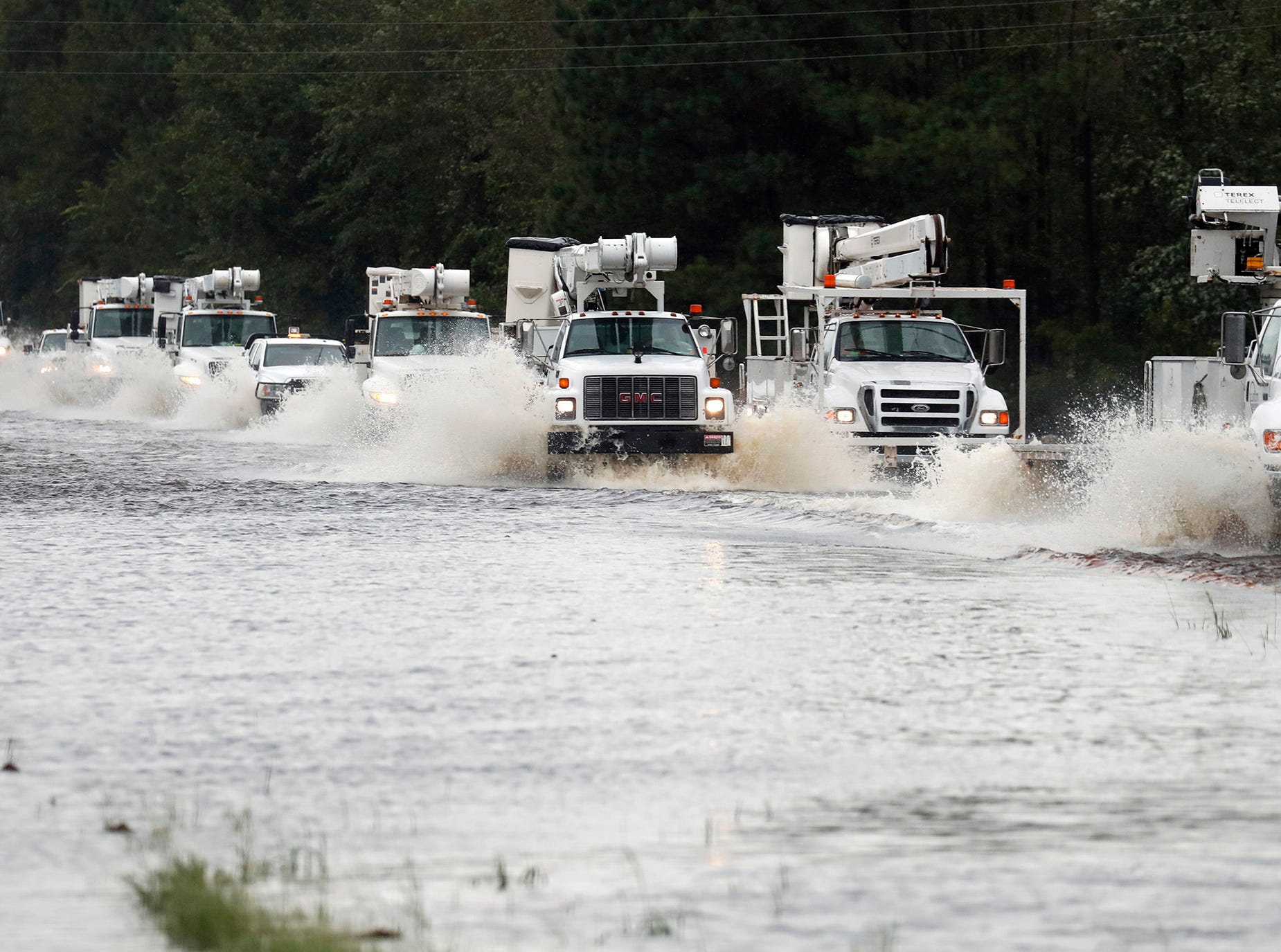 A convoy of utility trucks heading east to assist with damage caused by tropical storm Florence makes its way through a water covered stretch of U.S. Hwy. 70 east of Kinston, N.C., on Saturday Sept. 15, 2018. The road was closed to the public.