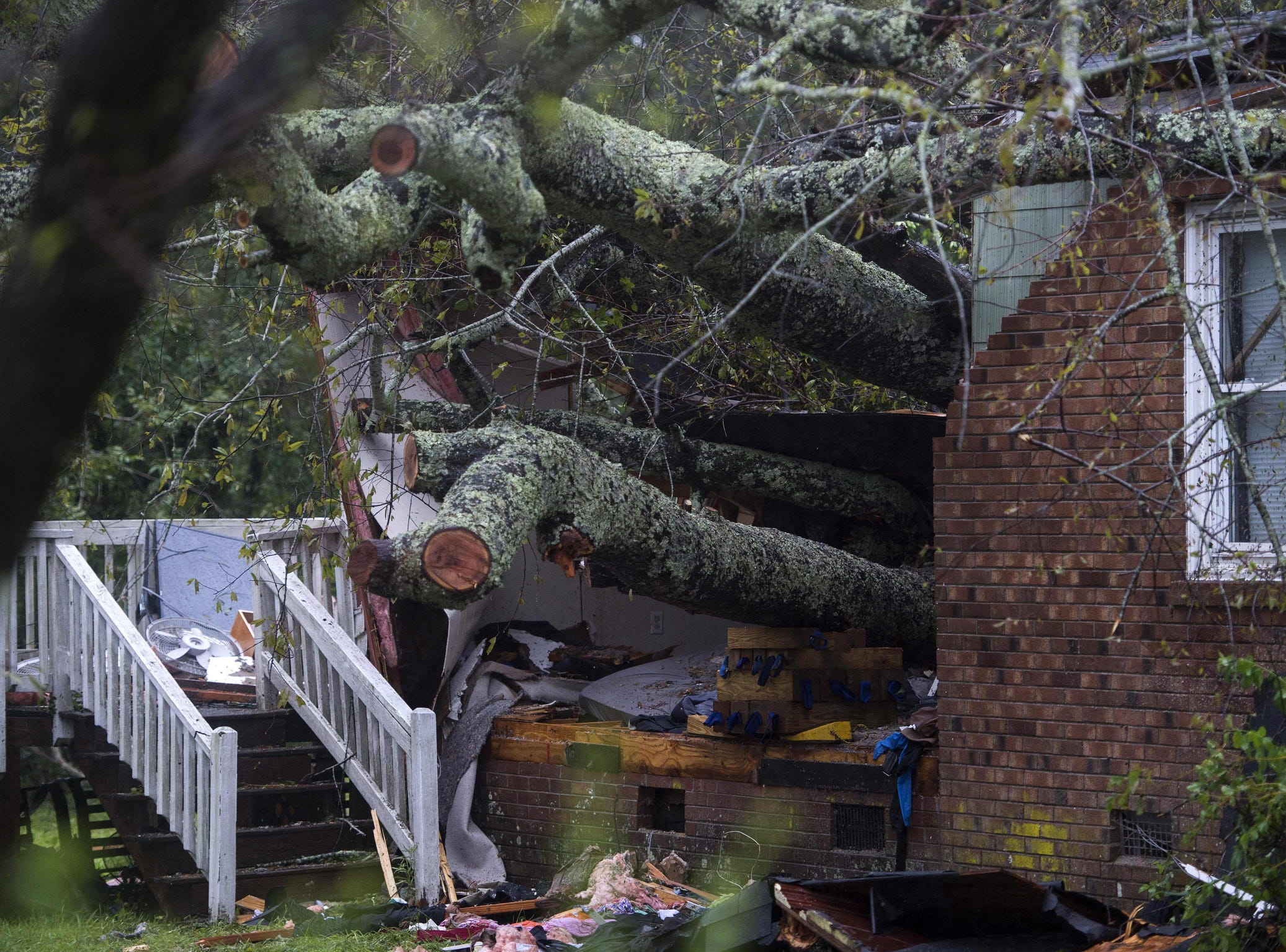 A tree that fell on a house, killing two people, is seen during Hurricane Florence in Wilmington, North Carolina on Sept. 14, 2018.  A mother and her infant were killed when a tree fell on their house, the first reported fatalities from Hurricane Florence, police said Friday. Wilmington police tweeted that the father was transported to the hospital with unspecified injuries.