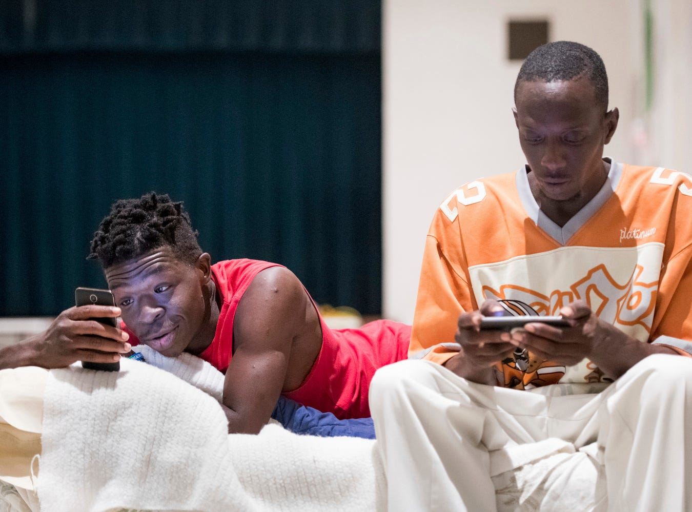 Eric Edwards Jr., left, and Elliott Farmer Jr. look at their phones from a blow up mattress at a storm shelter at Washington Street United Methodist Church as Florence slowly moved across the East Coast Friday, Sept. 14, 2018, in Columbia, S.C.