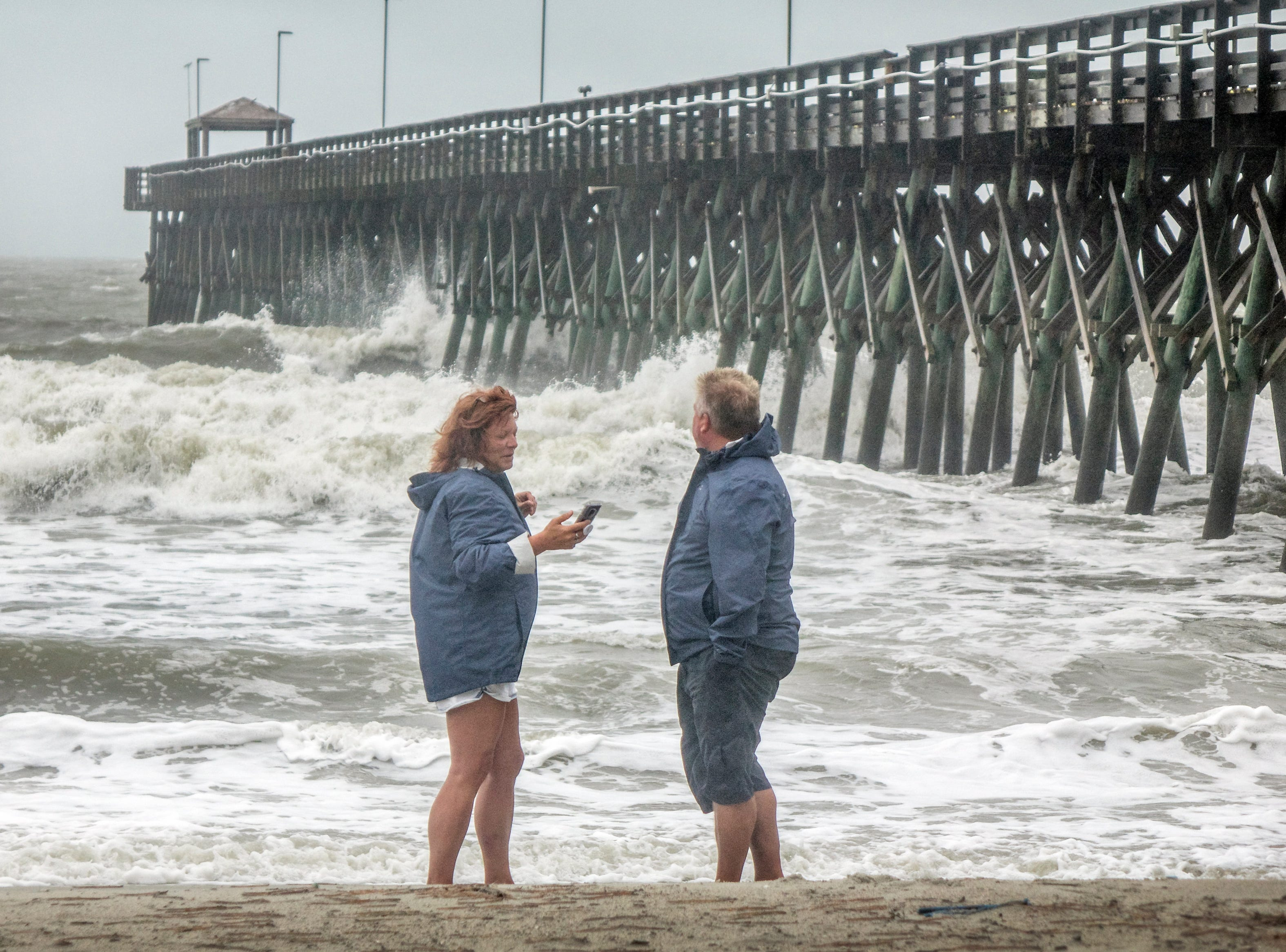 People walk on a beach in Myrtle Beach, S.C. on Sept. 2018. Hundreds of South Carolina's residents have decided to stay in their homes, ignoring the mandatory evacuation order.