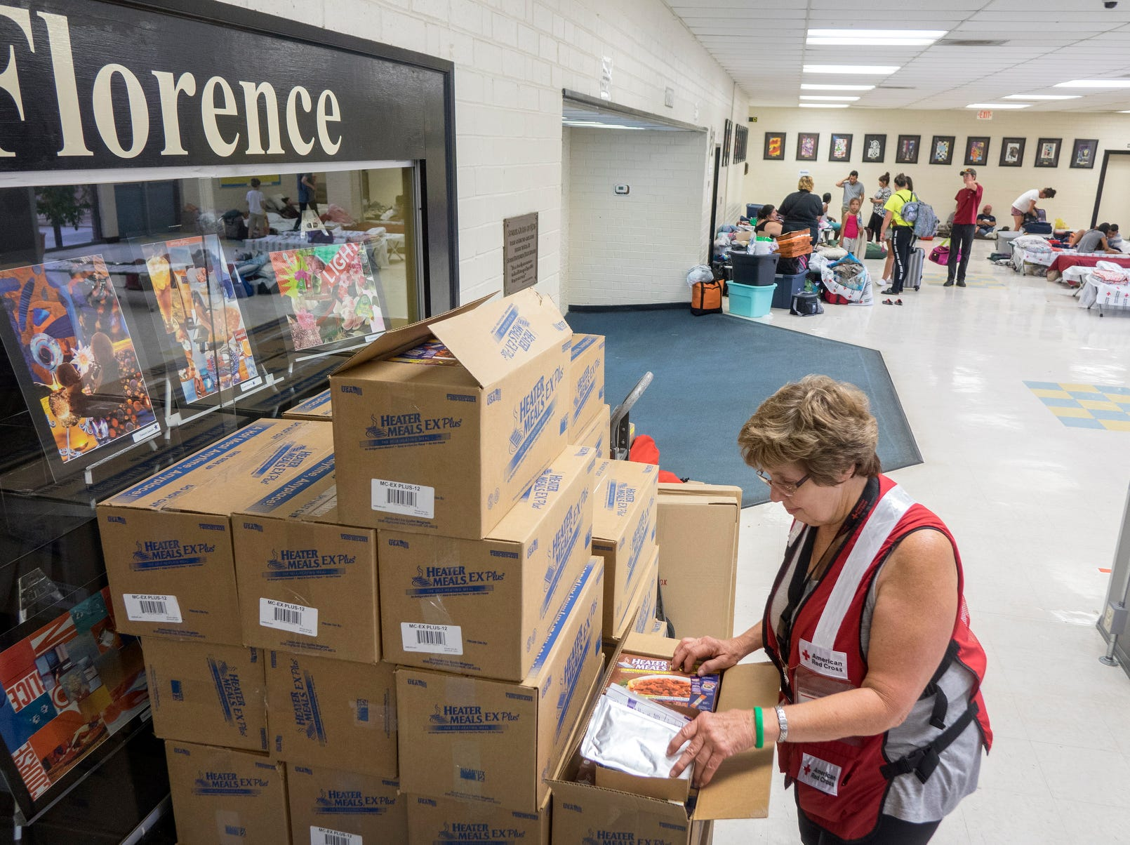 Dori Baumwart, from the American Red Cross Disaster Services, checks the emergency supplies at the hurricane shelter located in South Florence high school, Florence, S.C., Friday.