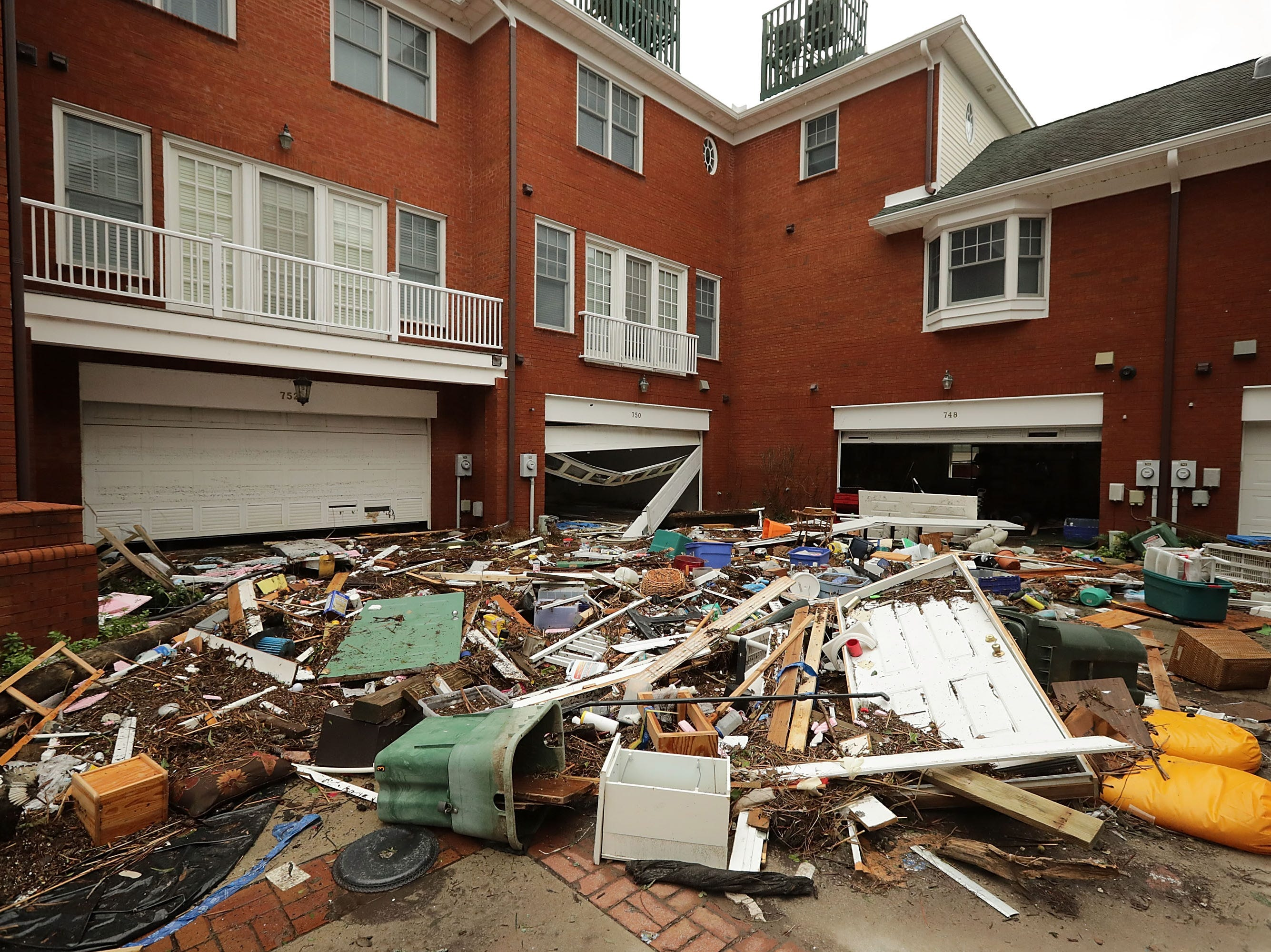 The courtyard at Queen's Point condos is filled with residents' belongings after the storm surge from Hurricane Florence tore open the lower floors with a four-foot high storm surge Sept. 15, 2018 in New Bern, N.C. Hurricane Florence made landfall in North Carolina as a Category 1 storm Friday and at least five deaths have been attributed to the storm, which continues to produce heavy rain and strong winds extending out nearly 200 miles.