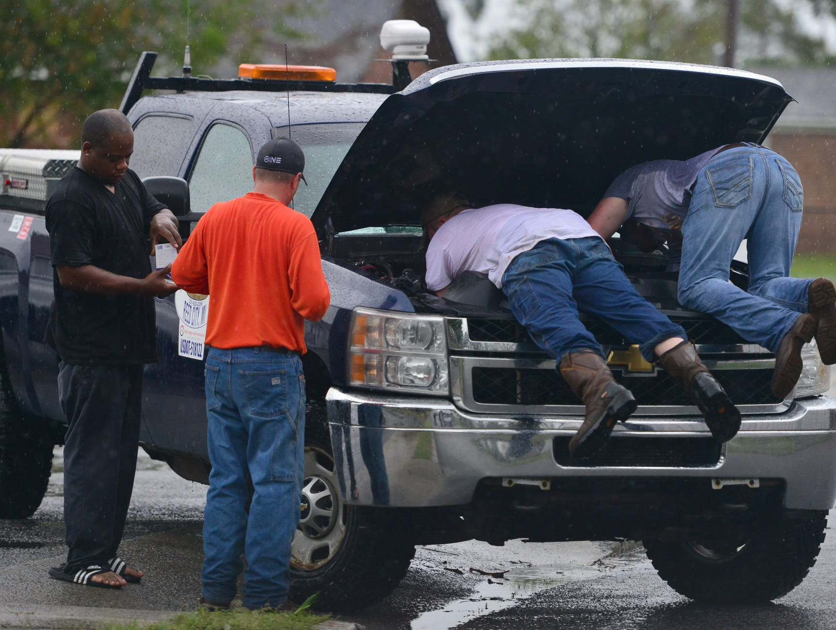 Workers try to fix their truck after driving through high water in Washington, N.C. on Friday afternoon.