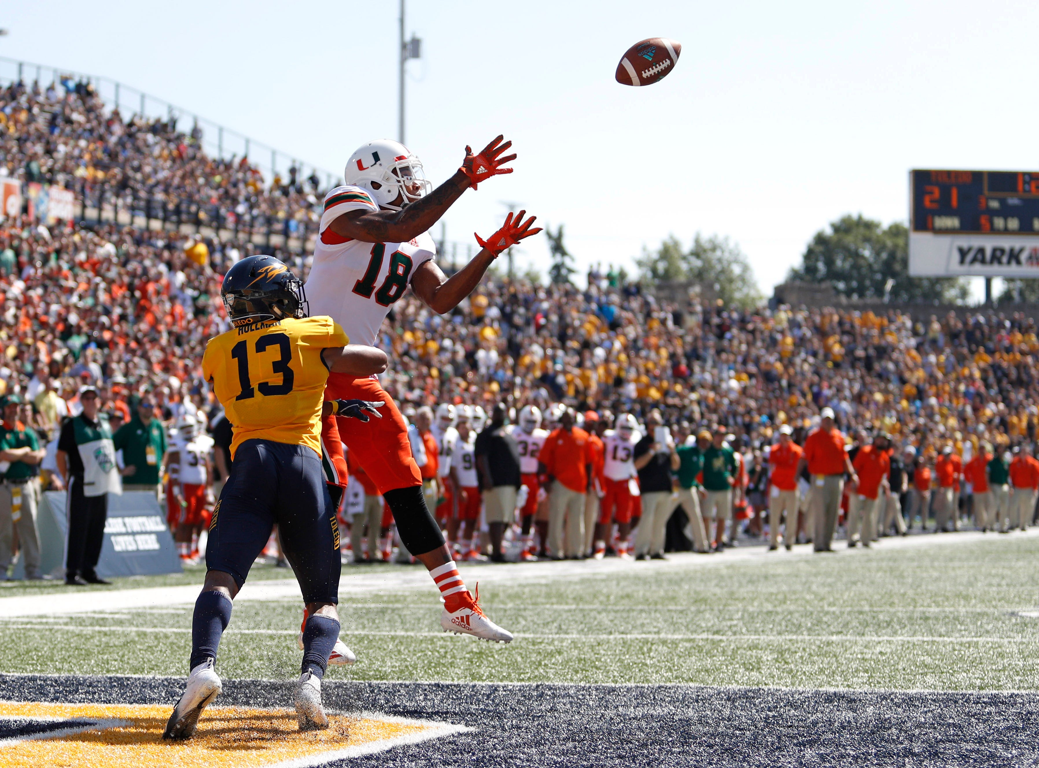 Miami Hurricanes wide receiver Lawrence Cager (18) makes a catch for a touchdown against Toledo Rockets cornerback Ka'dar Hollman (13) during the third quarter at Glass Bowl.