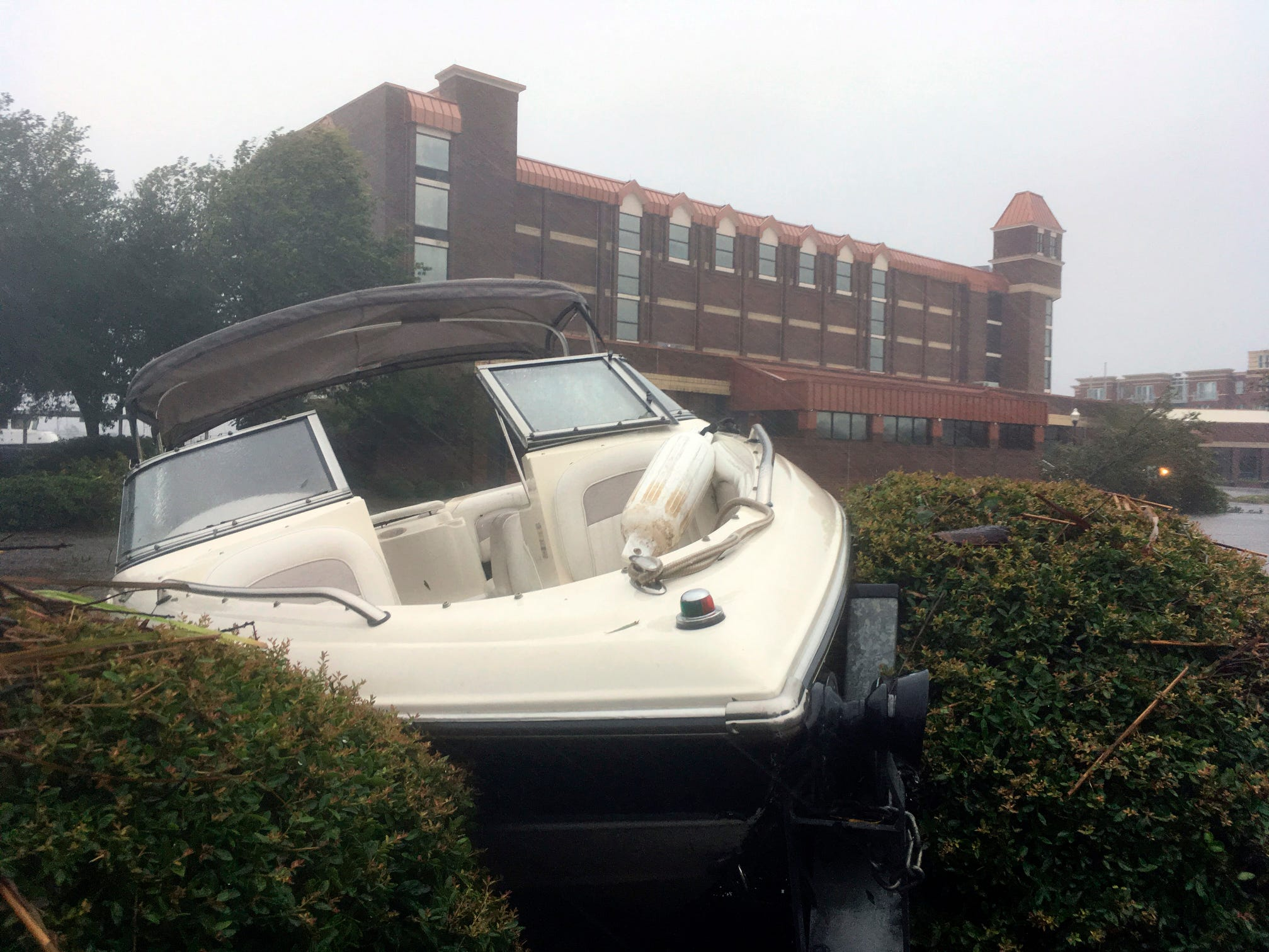 A speed boat sits wedged in bushes in the parking lot of a waterfront hotel in New Bern, N.C., on Frida. Winds and rains from Hurricane Florence caused the Neuse River to swell, swamping the coastal city.