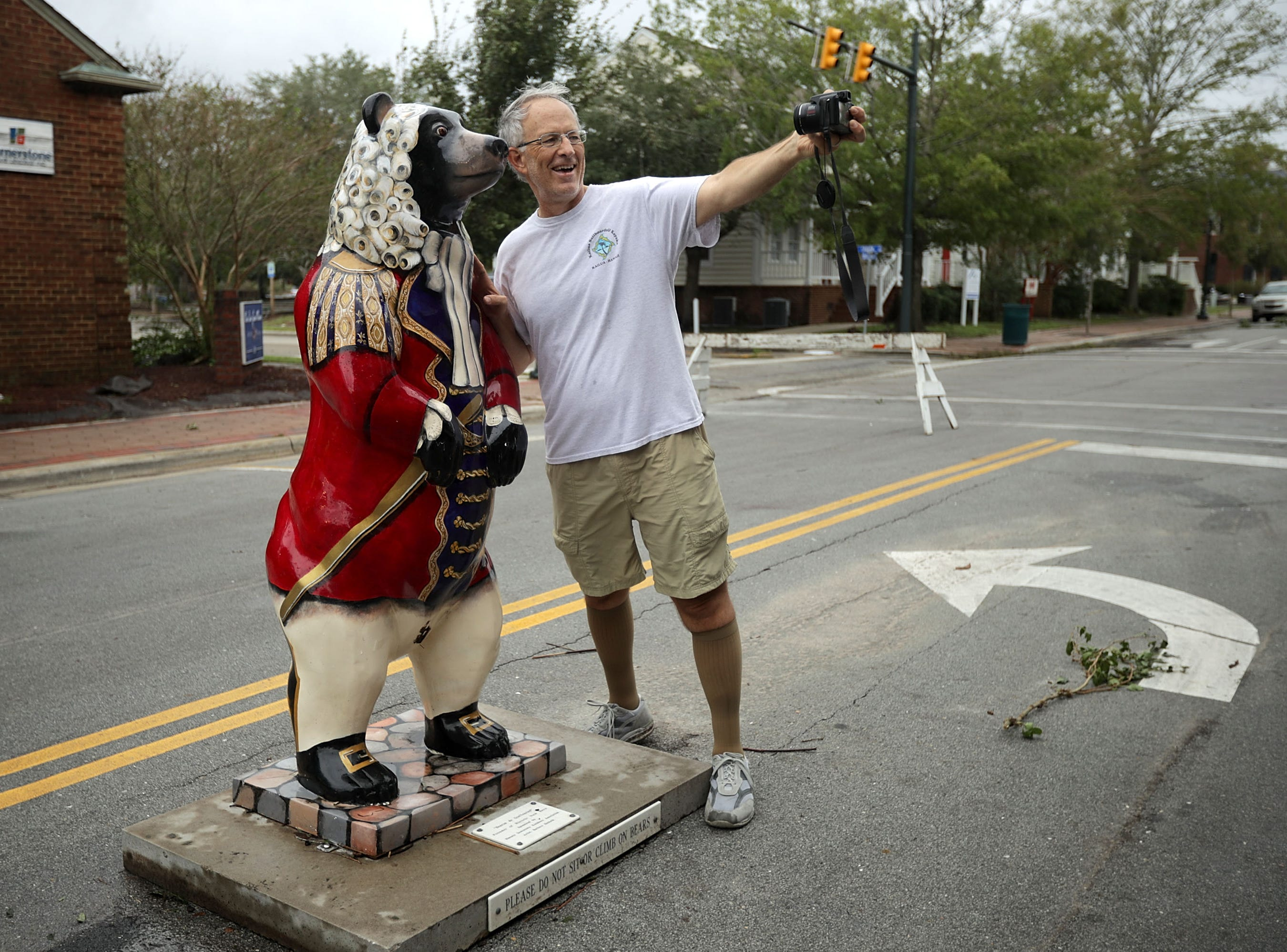 Rick Sitzman takes a selfie with the statue of a bear, the city's symbol, that was dropped in the middle of the street by storm surge produced by Hurricane Florence Sept. 15, 2018 in New Bern, N.C.