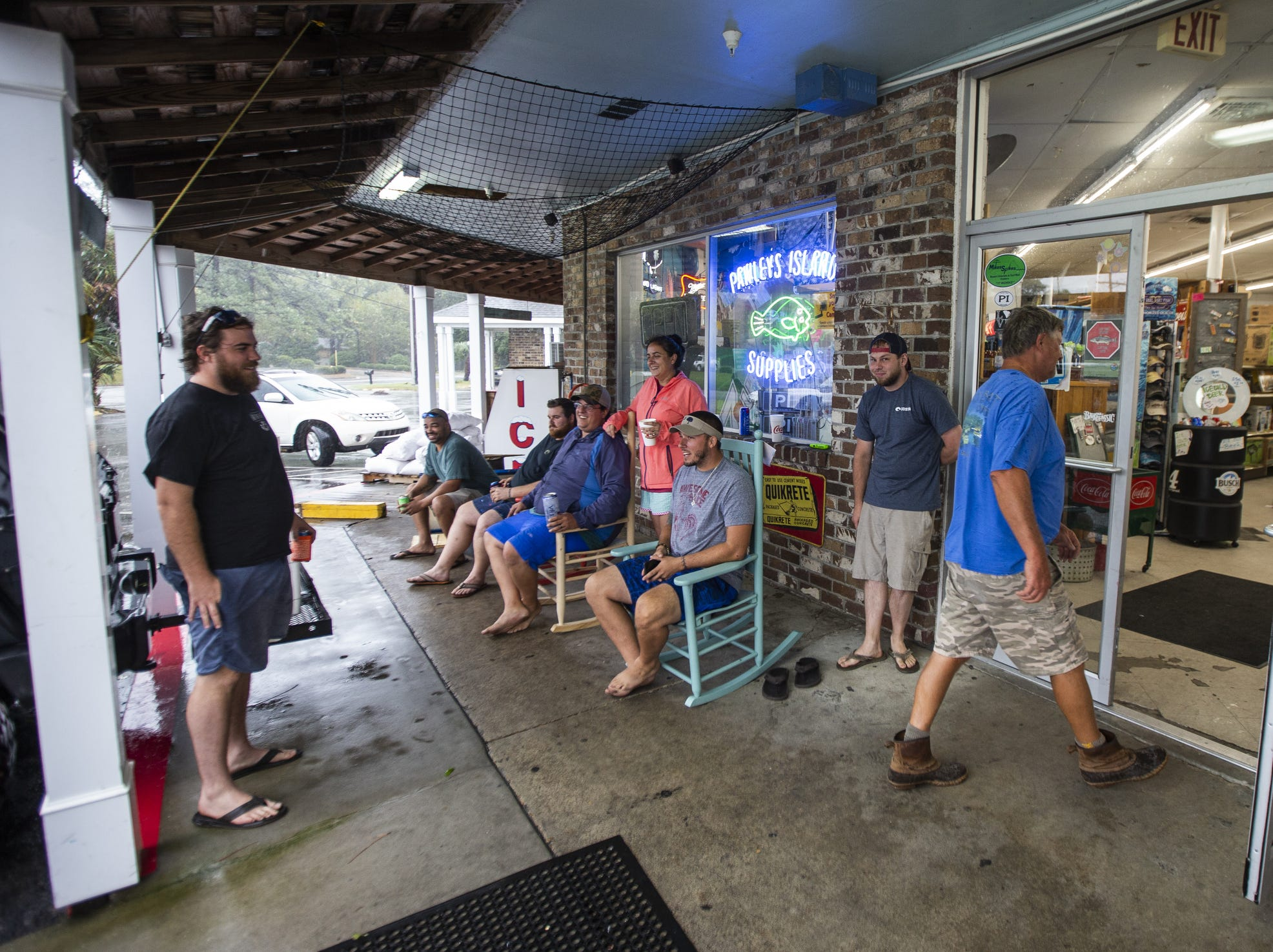 Local residents sit outside the Pawleys Island Supplies drinking beer as customers come and go at the only open store for miles around on Friday, in Pawleys Island, S.C.