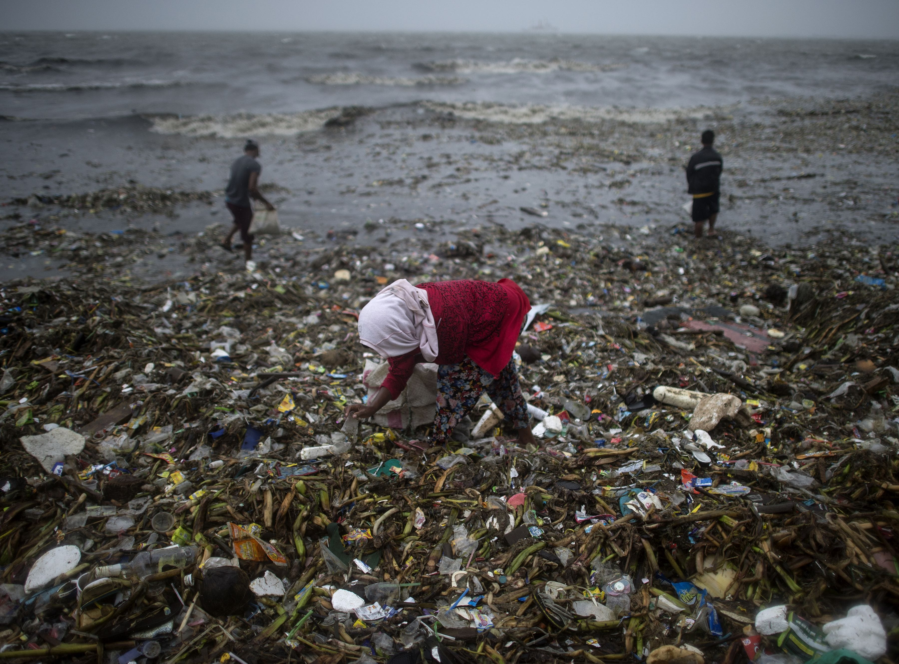 People collect recyclable materials washed ashore by strong waves caused by Super Typhoon Mangkhut at the Manila Bay on Sept. 15, 2018. Super Typhoon Mangkhut slammed into the northern Philippines, with violent winds and torrential rains, as authorities warned millions in its path of potentially heavy destruction.