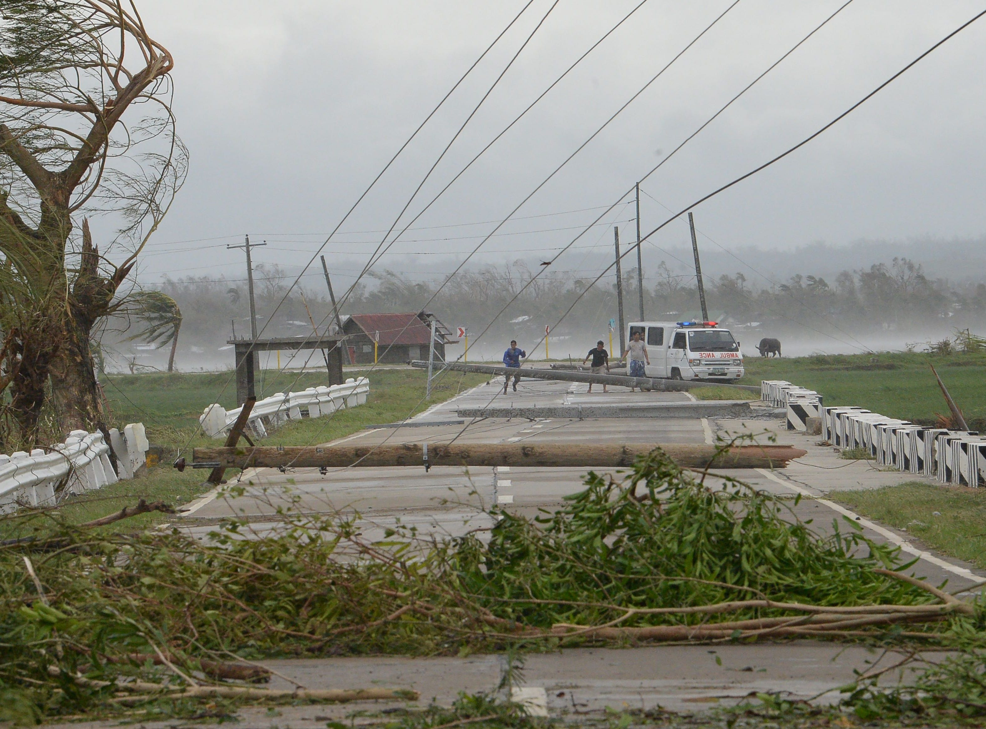 Staff of an ambulance carrying a sick child try to clear a road of debris and toppled electric posts caused by strong winds from super Typhoon Mangkhut along a road in Baggao in Cagayan province, north of Manila Sept. 15, 2018, as they try to bring the sick child to a nearby hospital of Tuguegarao city.