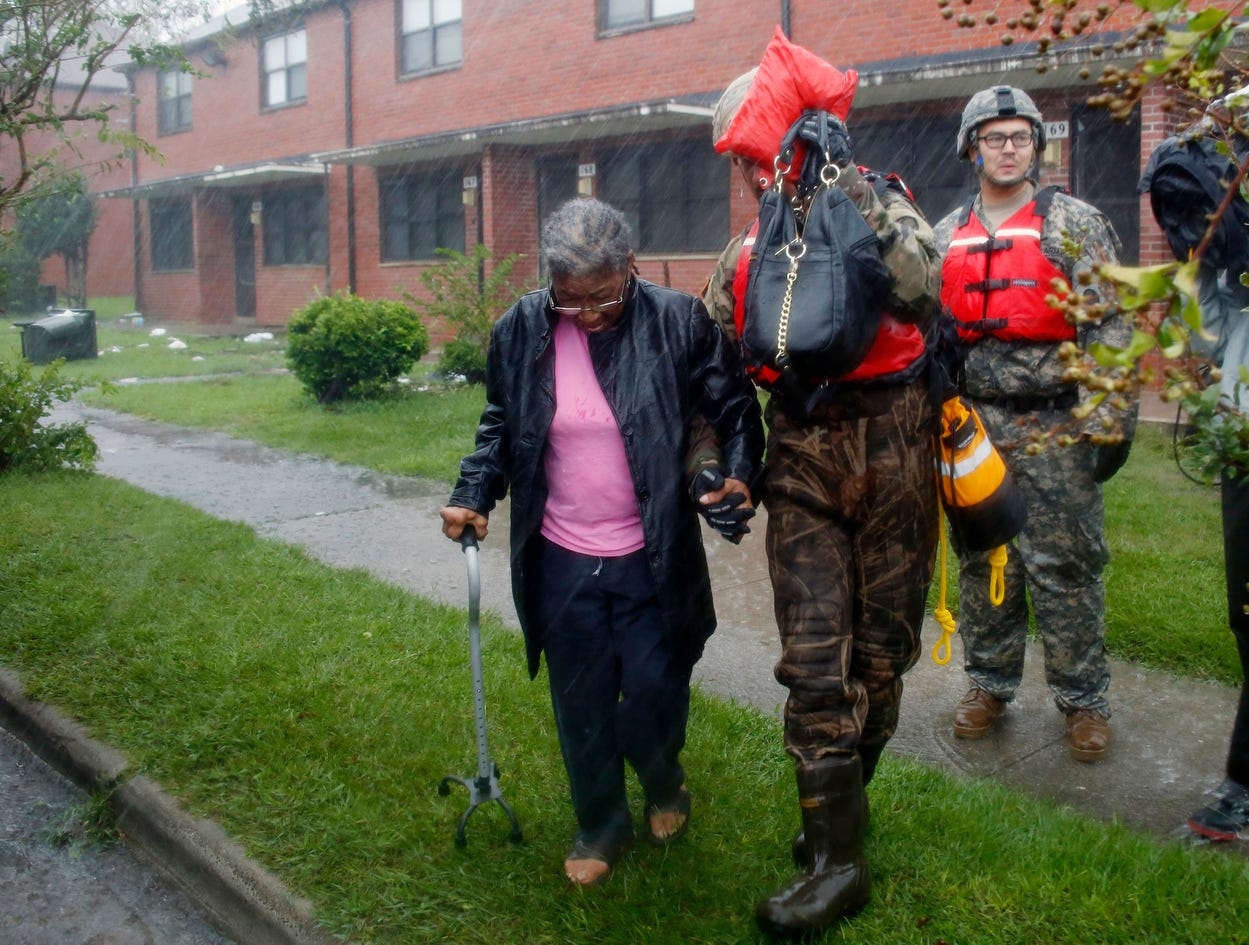 A rescue team from the North Carolina National Guard 1/120th battalion evacuates an elderly woman from her apartment as the rising floodwaters from Hurricane Florence threatens her home in New Bern, N.C., on Friday, Sept. 14, 2018.