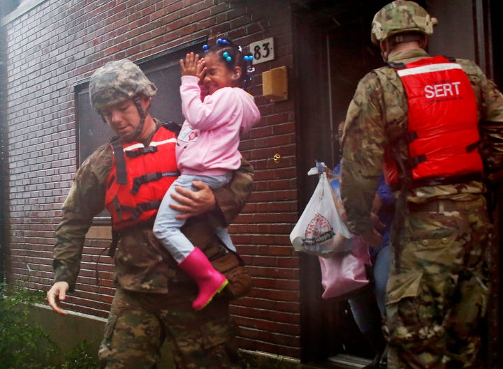 A rescue team from the North Carolina National Guard 1/120th battalion evacuates a family as the rising floodwaters from Hurricane Florence threatens their home in New Bern, N.C..