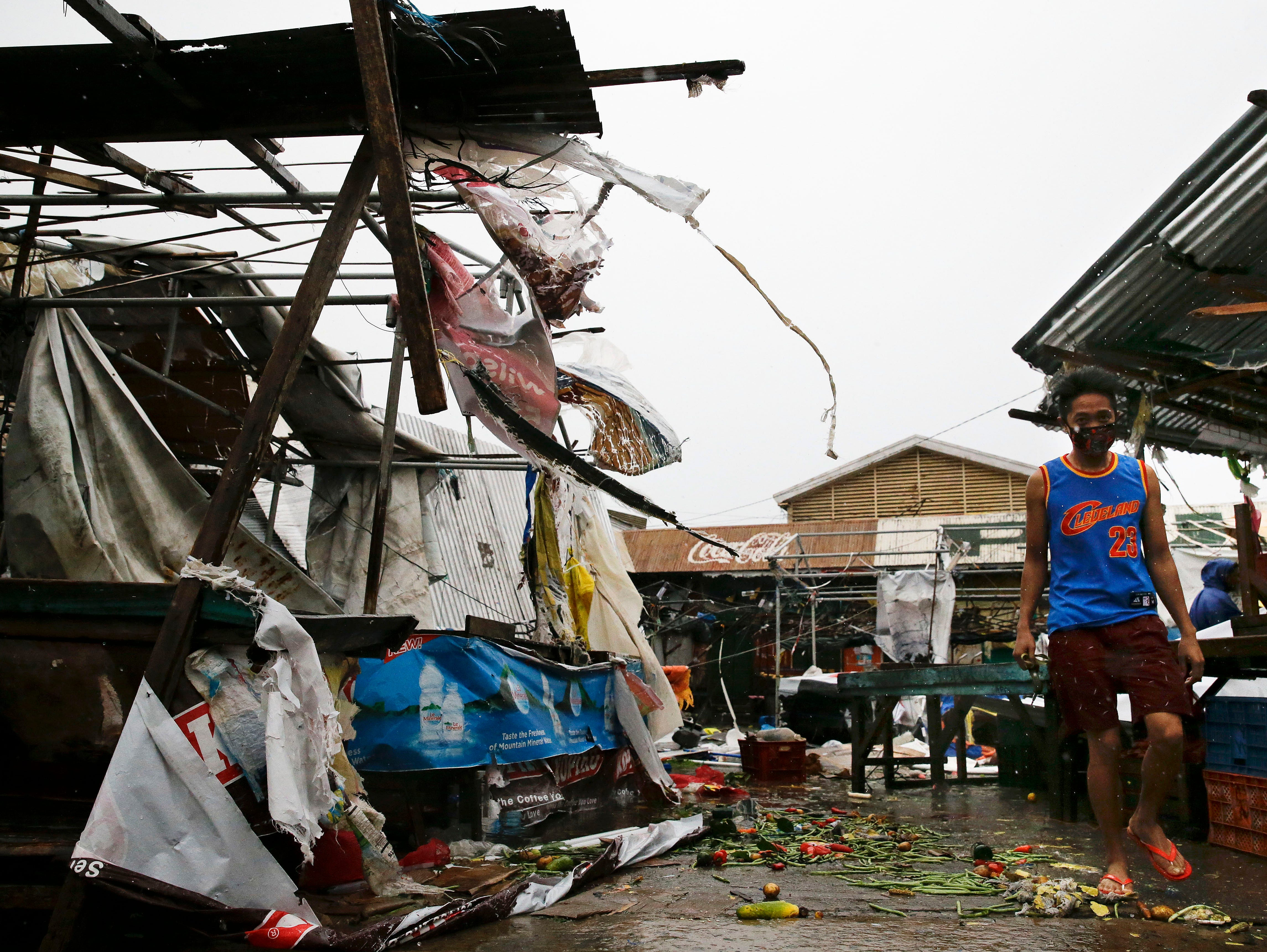 A resident walks along destroyed stalls at a public market due to strong winds as Typhoon Mangkhut barreled across Tuguegrao city in Cagayan province, northeastern Philippines on Saturday, Sept. 15, 2018. The typhoon slammed into the Philippines northeastern coast early Saturday, it's ferocious winds and blinding rain ripping off tin roof sheets and knocking out power, and plowed through the agricultural region at the start of the onslaught.