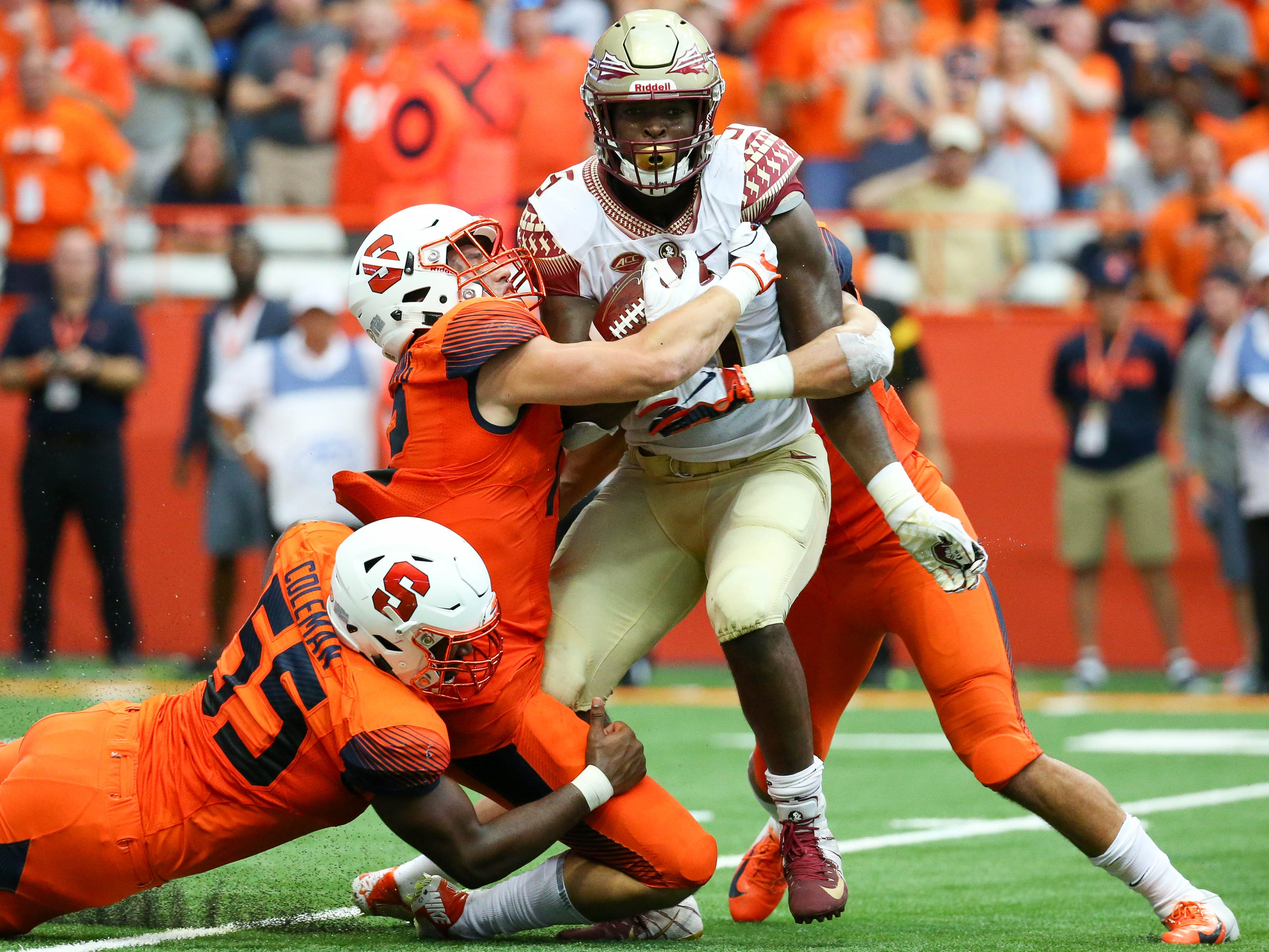 The Syracuse defense, led by defensive lineman Kendall Coleman (55), stops Florida State running back Jacques Patrick (9) during the second quarter Saturday at the Carrier Dome.