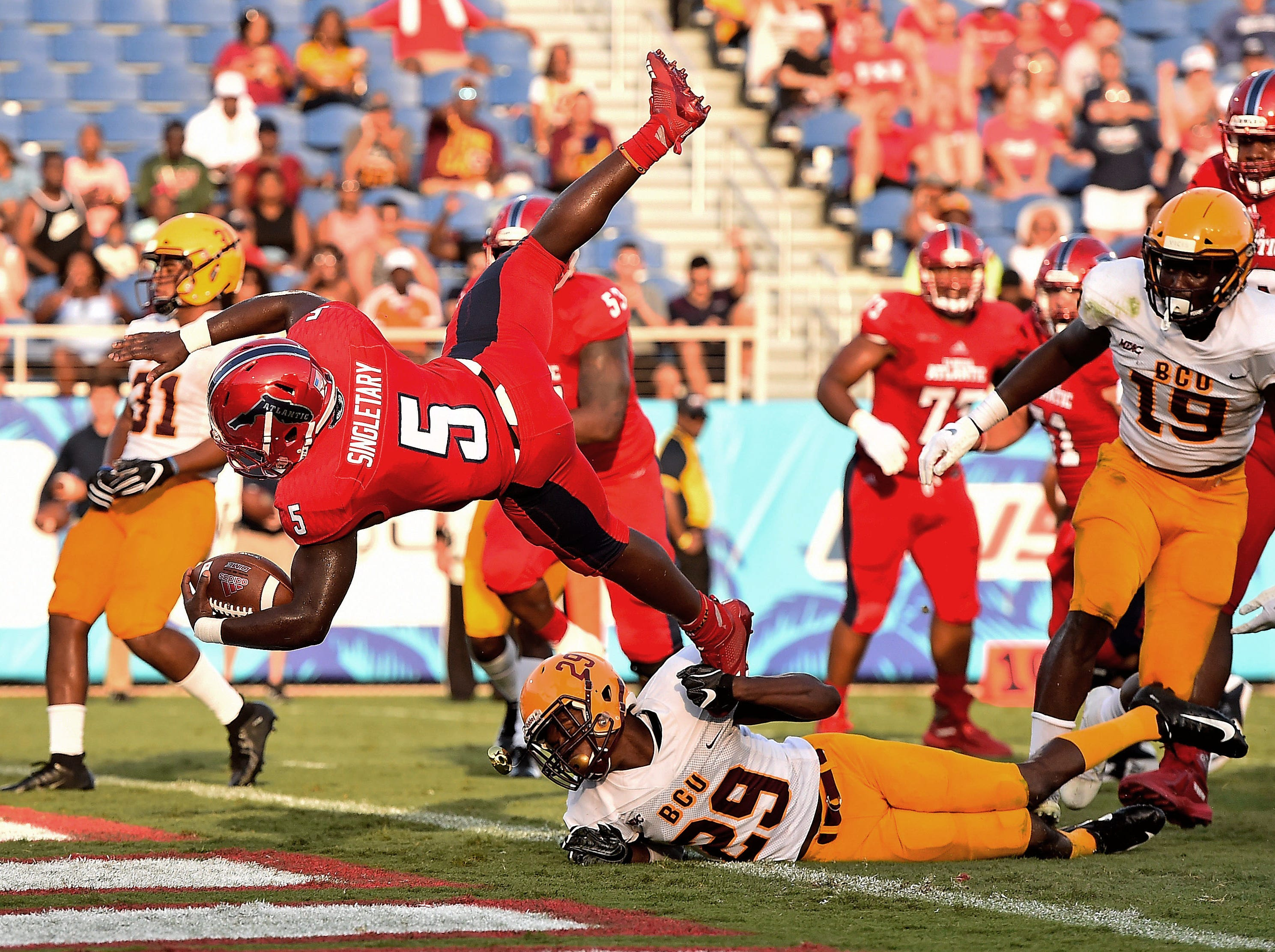 Florida Atlantic Owls running back Devin Singletary (5) leaps over Bethune Cookman Wildcats cornerback Jamauri Laguerre (29) to score a  touchdown during the first half at FAU Football Stadium.