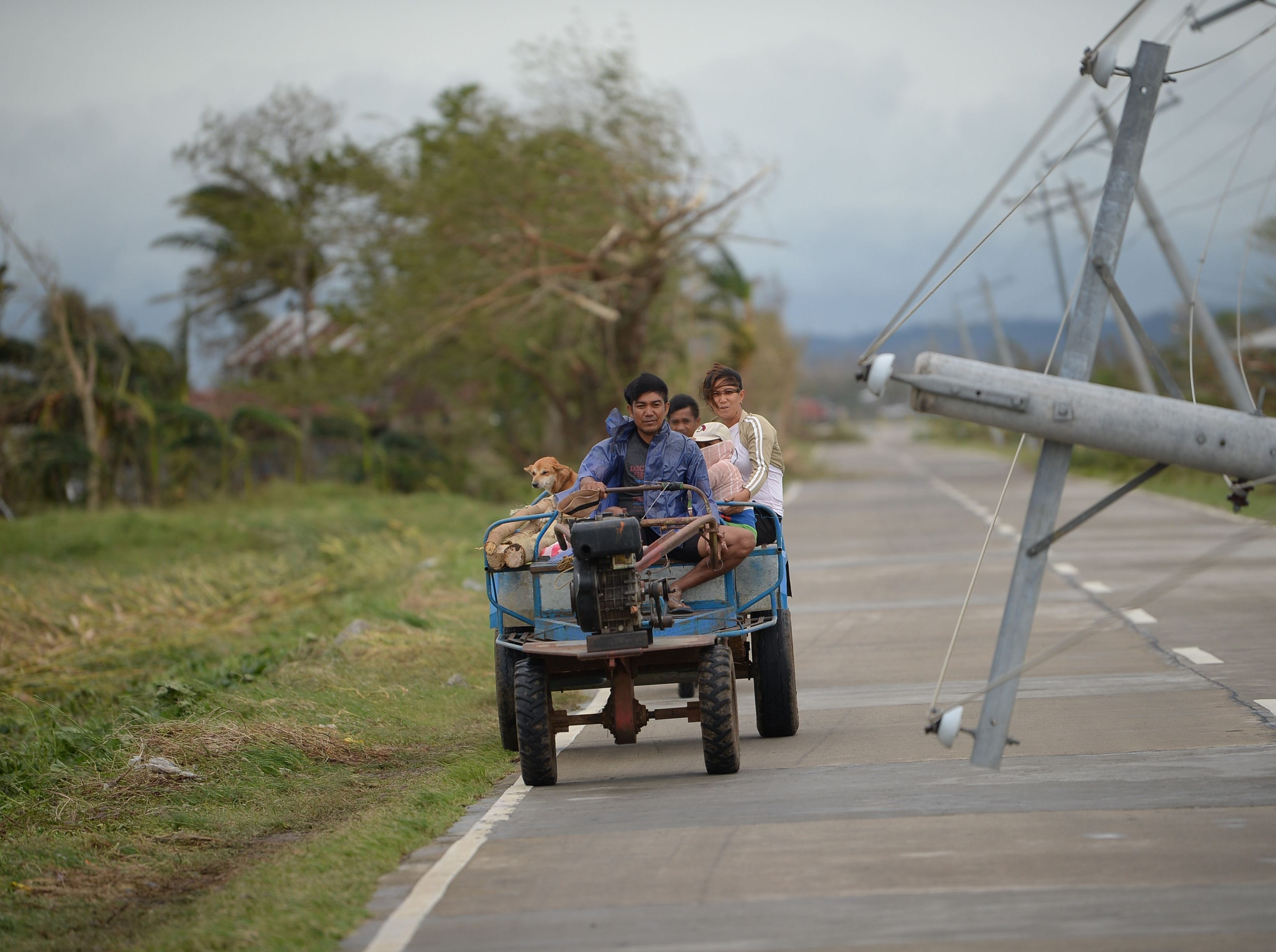 A family commute on an improvised vehicle past an electric post toppled by strong winds from Super Typhoon Mangkhut in Baggao, Cagayan province on Sept. 15, 2018.