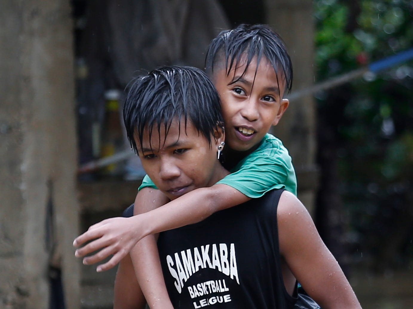 A teenager carries his friend in floodwaters in San Mateo town of Rizal Province, east of Manila, Philippines on Sept. 15, 2018.