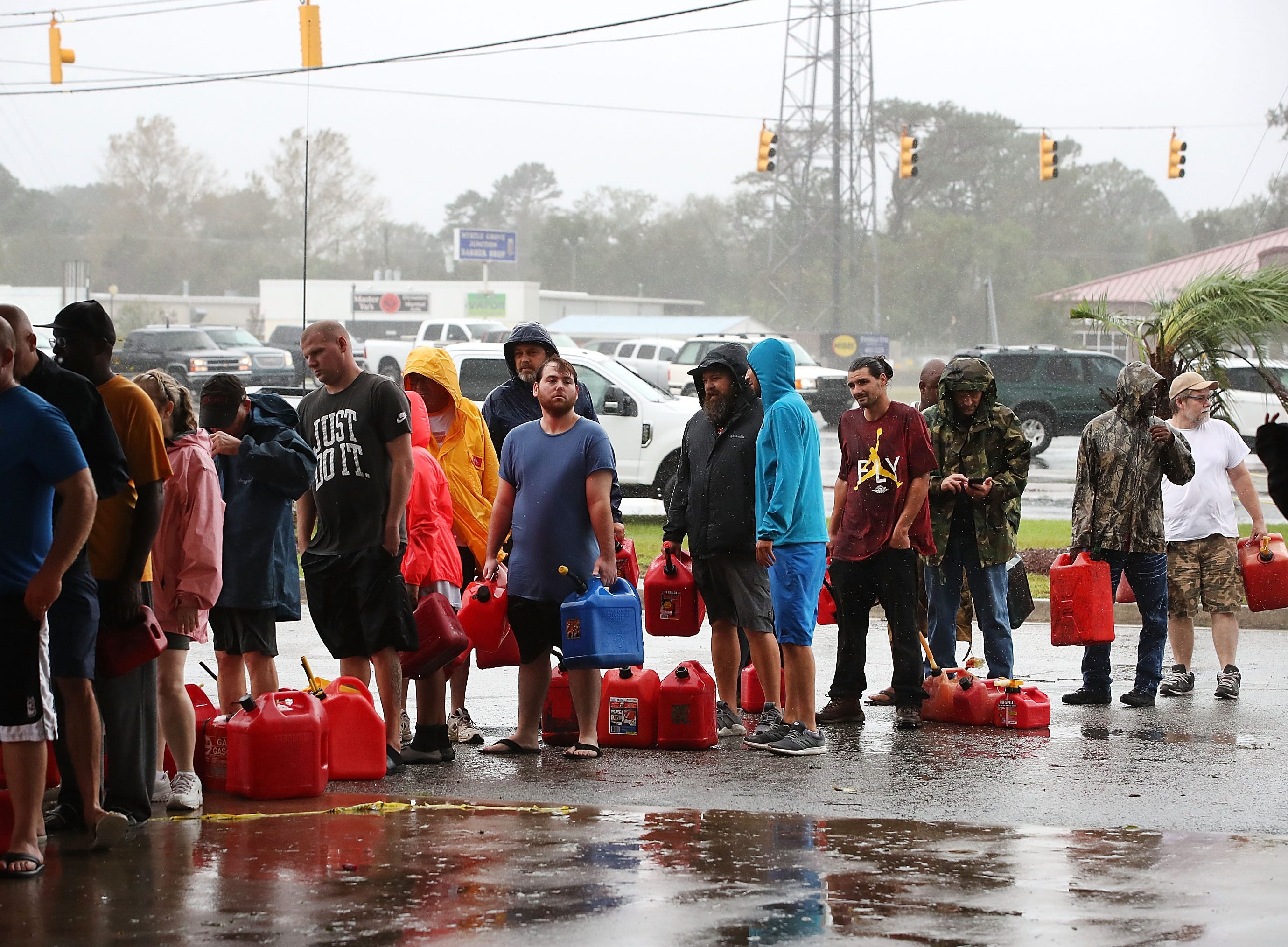 People wait in line to fill up their gas cans at a gas station that was damaged when Hurricane Florence hit the area, on Sept. 15, 2018 in Wilmington, N.C..