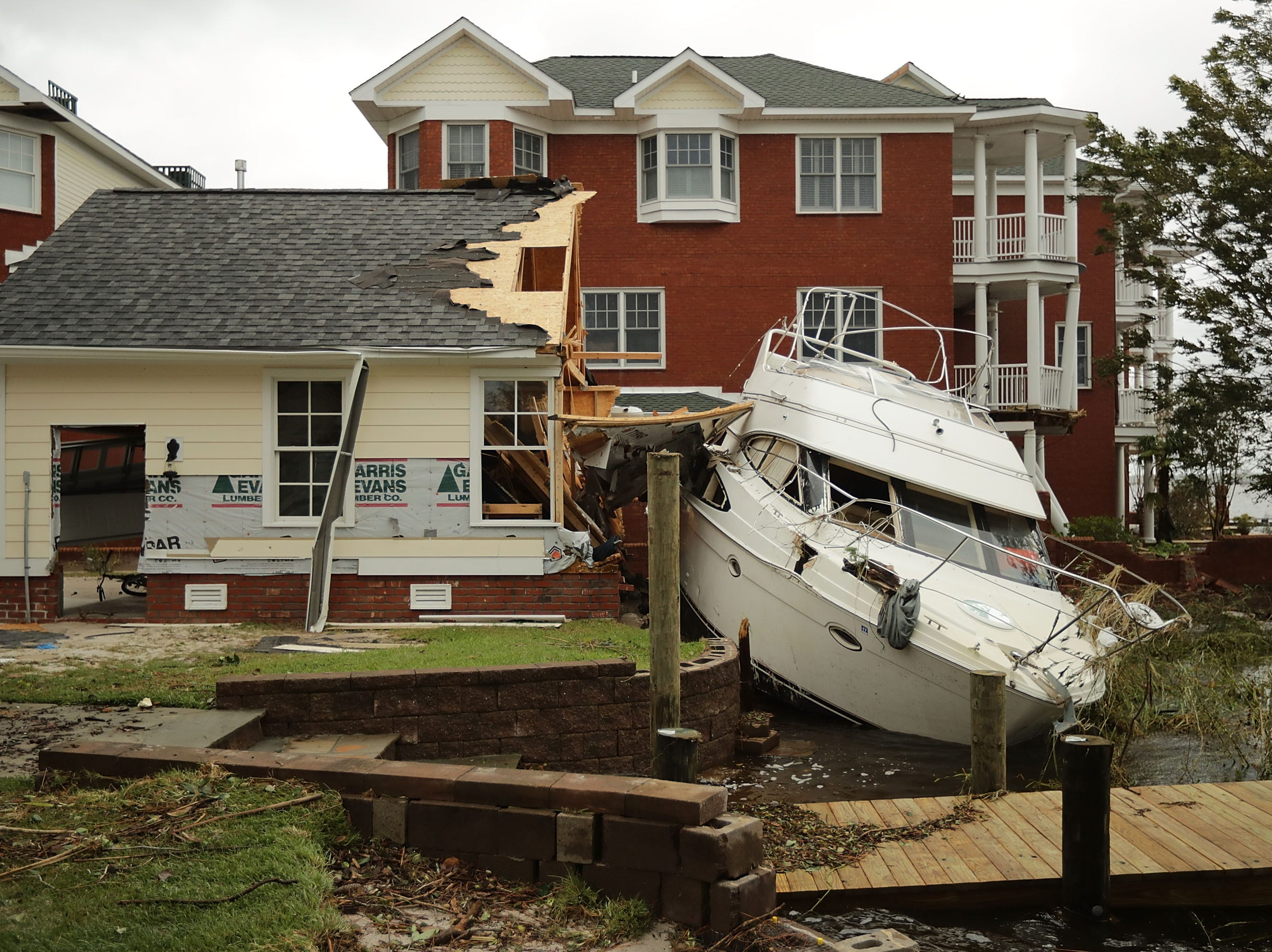 A boat lays smashed against a car garage, deposited there by the high winds and storm surge from Hurricane Florence along the Neuse River Sept. 15, 2018 in New Bern, N.C.