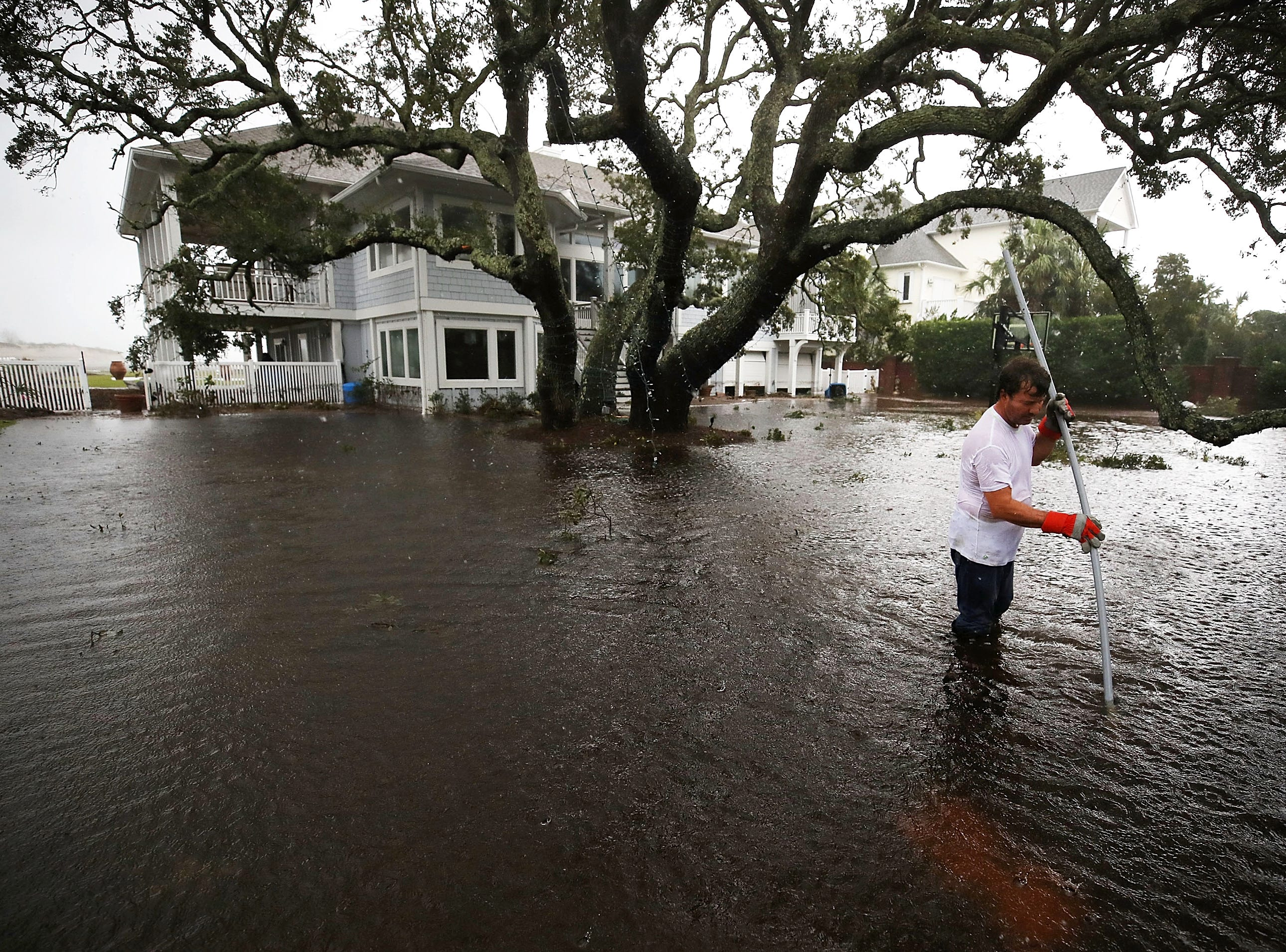 Mike Pollack searches for a drain in the yard of his flooded waterfront home a day after Hurricane Florence hit the area, on Sept. 15, 2018 in Wilmington, N.C..