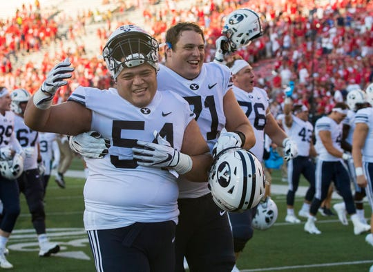 BYU Cougars defensive lineman Merrill Taliauli (54) and offensive lineman Austin Hoyt (71) celebrate their upset of the Wisconsin Badgers at Camp Randall Stadium.