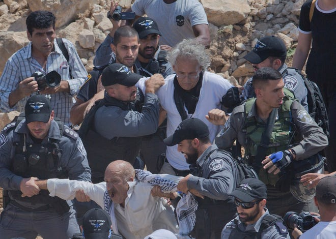 n this Friday, Sept. 14, 2018 file photo, Israeli border police arrest American university professor Frank Romano, center top, in the West Bank Bedouin community of Khan al-Ahmar. A lawyer for Romano says he was detained by Israeli police for allegedly trying to disrupt the work of security forces in the embattled community of Khan al-Ahmar. (AP Photo/Nasser Nasser, File) ORG XMIT: DV102
