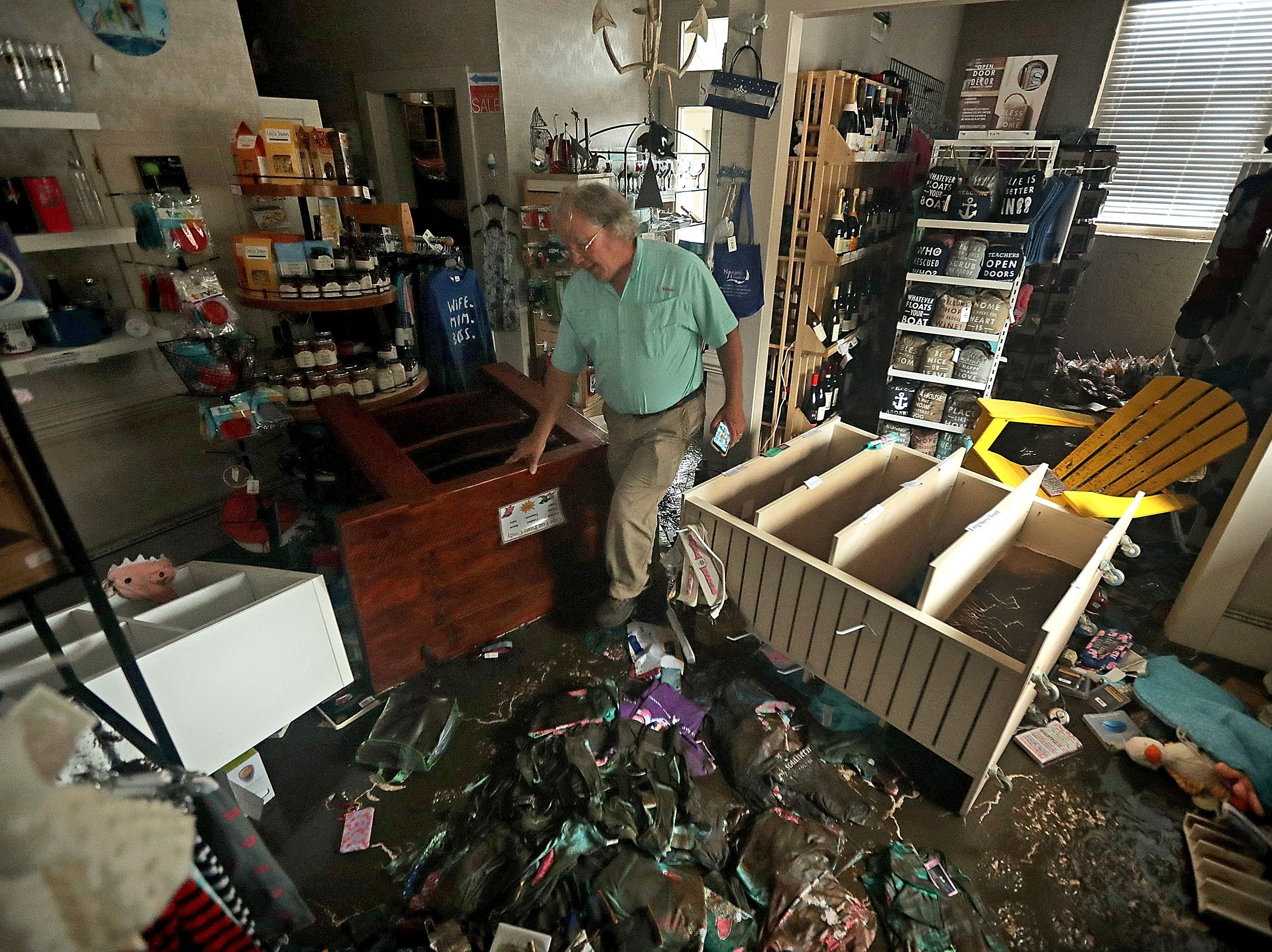 Bill Wheeler makes a video recording of the damage to his store, Nautical Wheelers, after the storm surge from Hurricane Florence filled it with four feet of water on Sept. 15, 2018 in New Bern, N.C.
