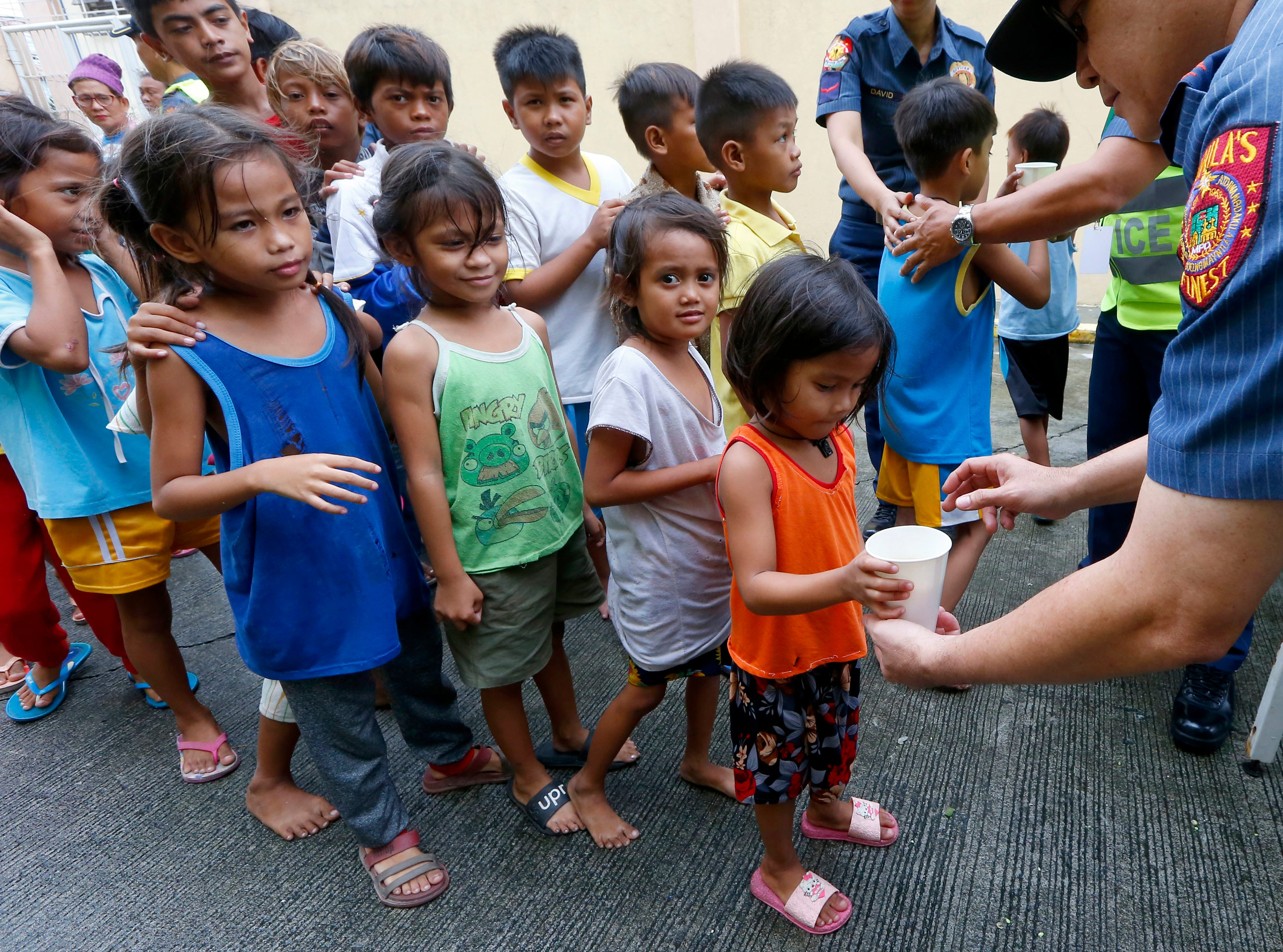 Manila police give out rice porridge to residents living along the coastal community of Baseco as they evacuate during the onslaught of Typhoon Mangkhut which barreled into northeastern Philippines before dawn Saturday, Sept. 15, 2018 in Manila, Philippines.