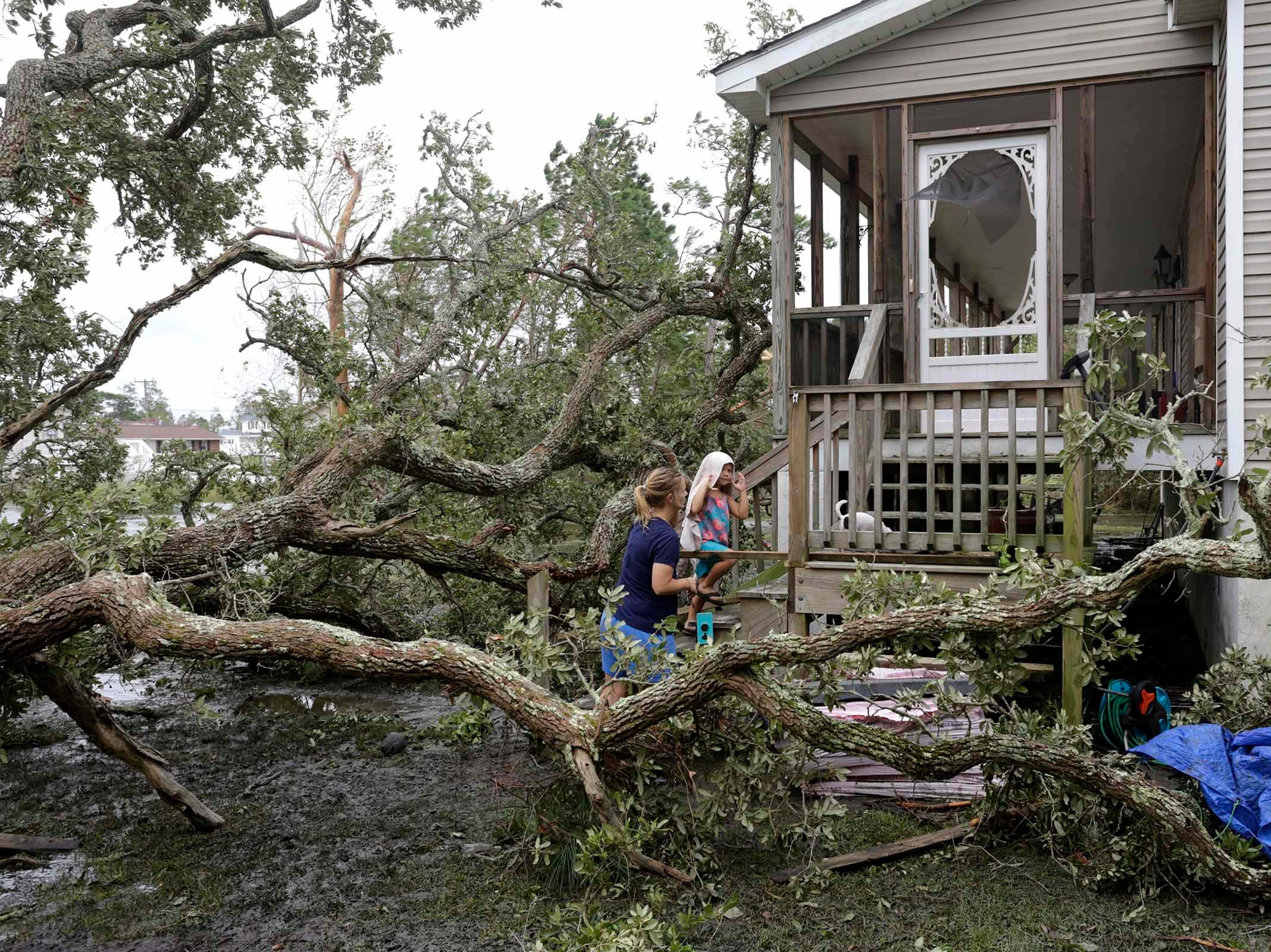 Jessie Lawrence and her daughter Kinsley Spaid make their way home after Hurricane Florence hit Davis N.C.,Saturday, Sept. 15, 2018. Davis was said to have 4 1/2 feet of storm surge.