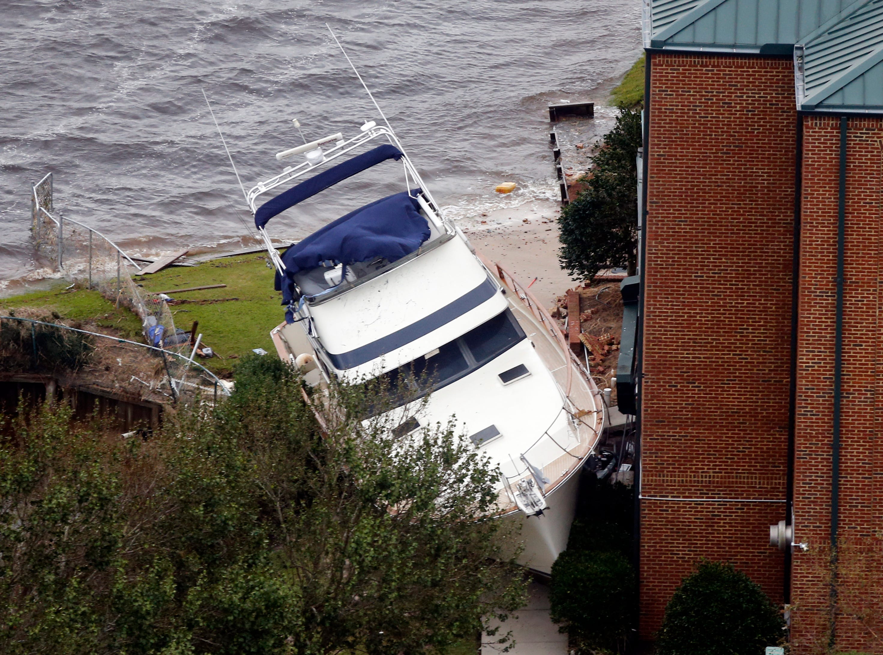 A yacht sits on the Neuse river bank next to a hotel after hurricane Florence passed through the area in New Bern, NC., Saturday, Sept. 15, 2018.