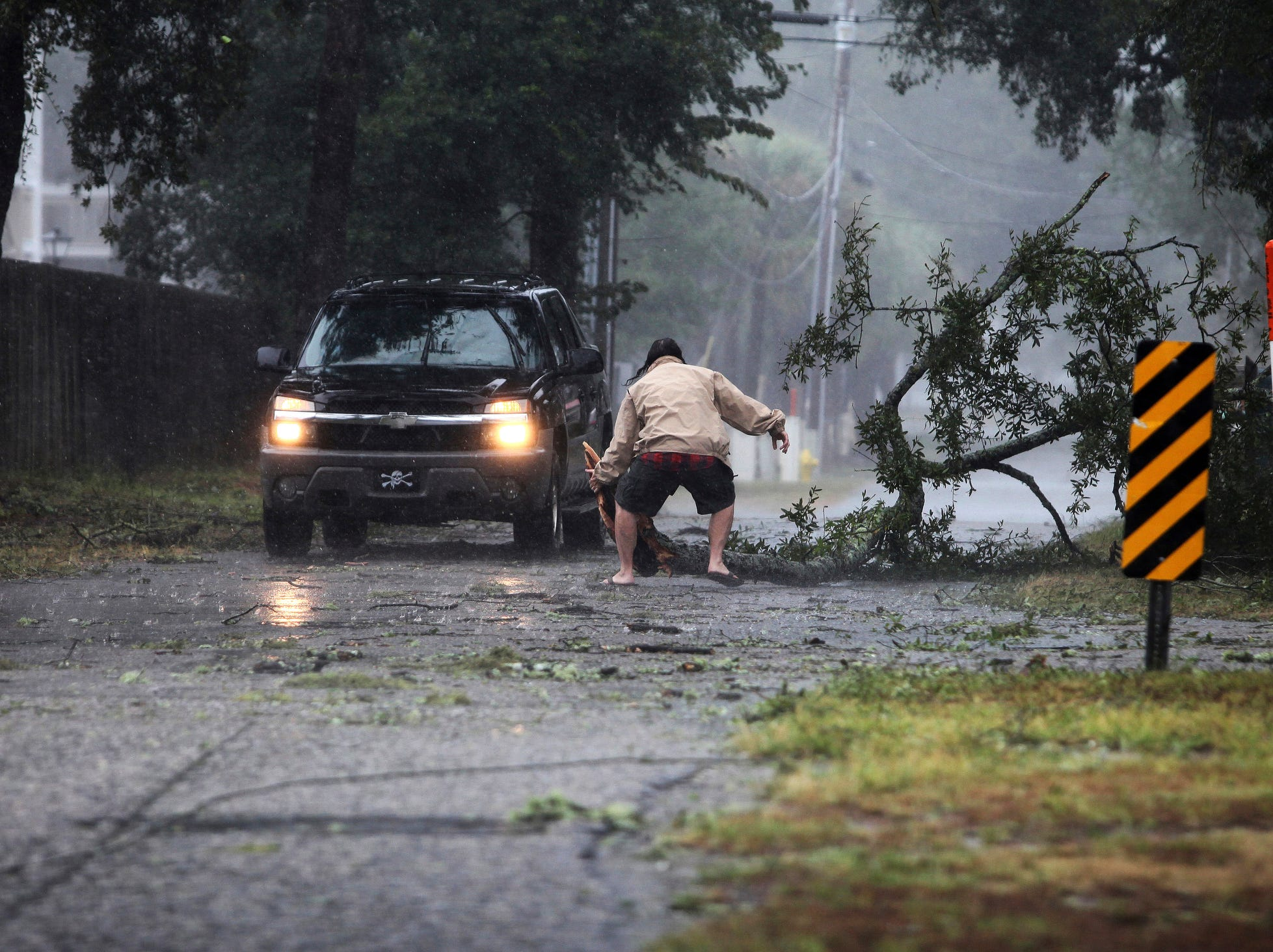A man moves a large tree limb that downed power lines as the hurricane-turned-tropical storm Florence hit the Cherry Grove community in North Myrtle Beach, S.C., Friday.