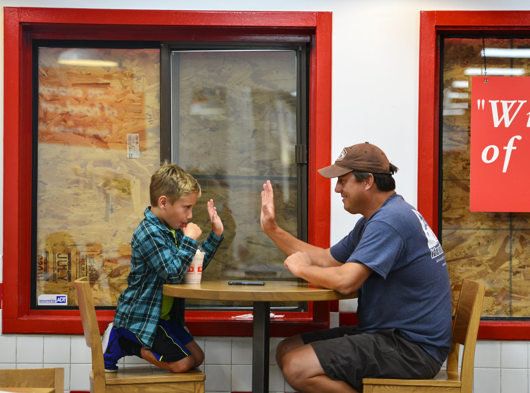 Sitting next to a boarded up window, Grant Lefevre, 7 of Kitty Hawk, N.C., plays tic tac toe with his father Alex at Five Guys, which is one of the only restaurants open in the Outer Banks, Friday afternoon. The Lefevre family has been holed up in their home since Wednesday and this was their first meal outside of their home.