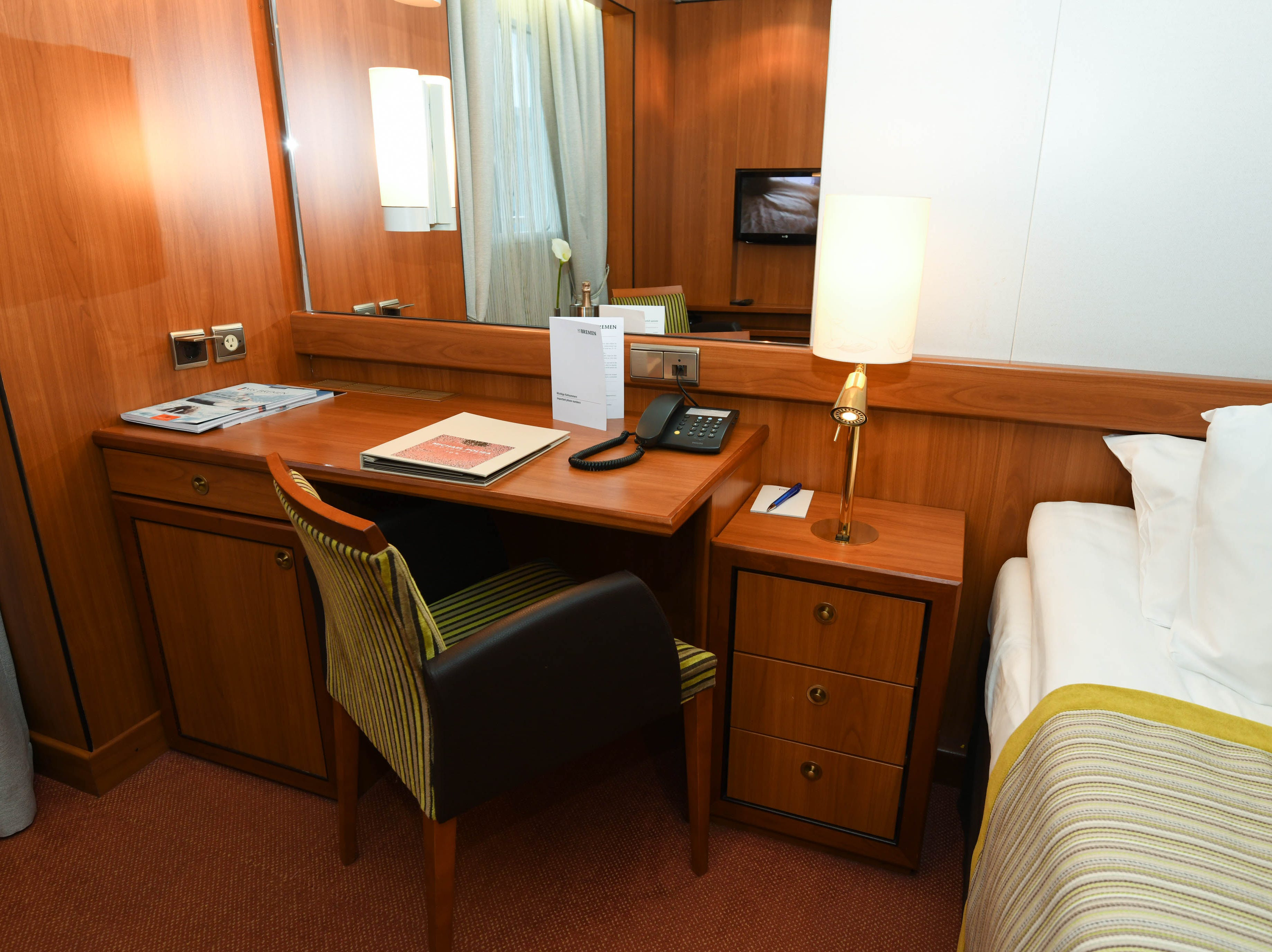The built-in desks in Bremen cabins come with telephones that can be used for calling for room service. End tables with drawers sit on each side of the bed.