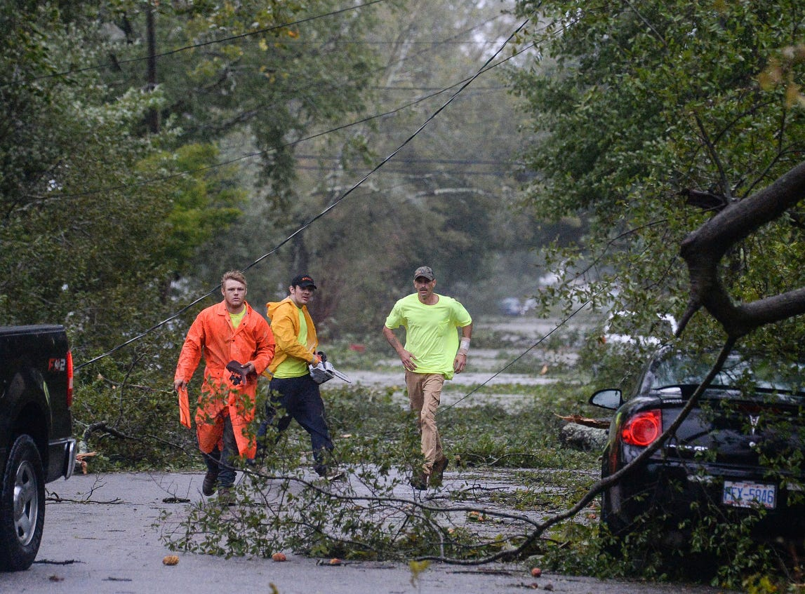Men from a tree cutting service help clear a blocked road near downtown Wilmington, N.C., Friday.