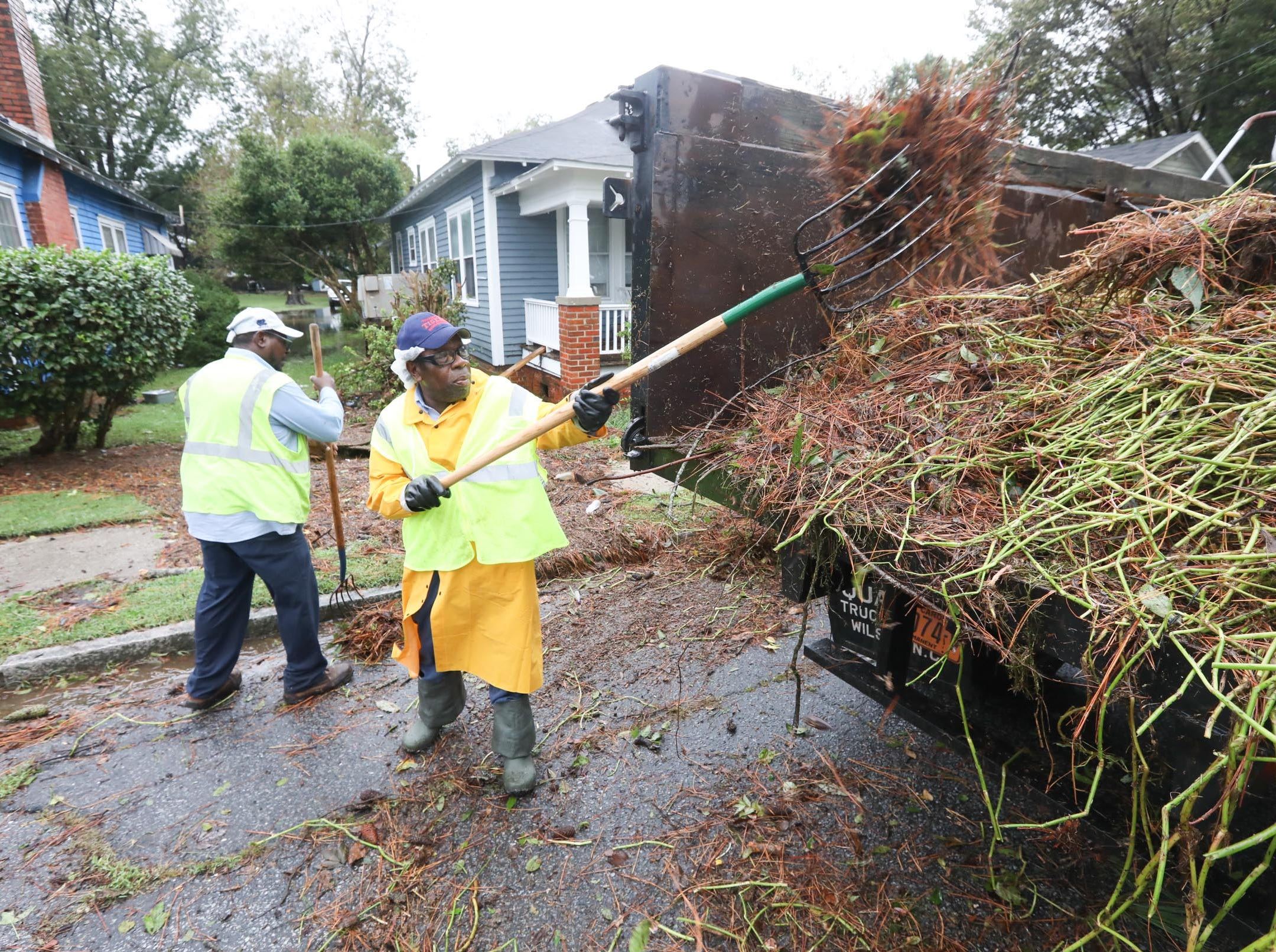 Public Works Department worker Noah Clark uses a pitch fork to remove debris from East Second St. in Washington, N.C. on Saturday, Sept. 15, 2018.