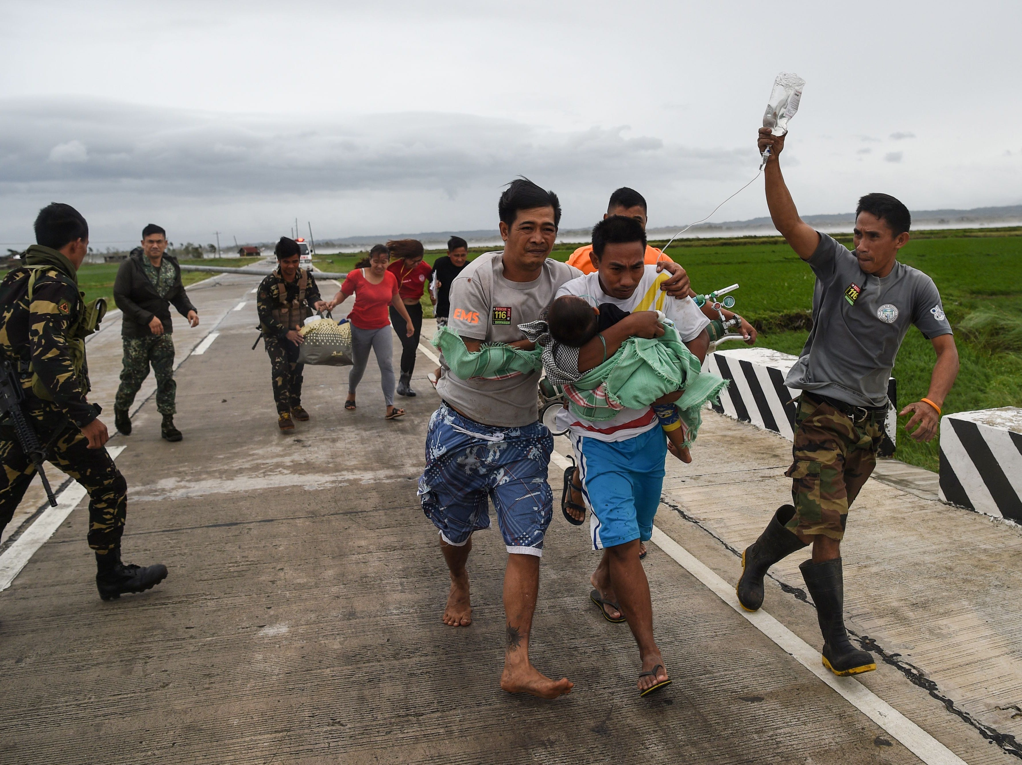Philippine soldiers assist a family carrying their sick child to a waiting government vehicle after their ambulance failed to make it through a road blocked with fallen tree debris and electric posts toppled by strong winds from Super Typhoon Mangkhut in Baggao, Cagayan province on Sept.15, 2018.