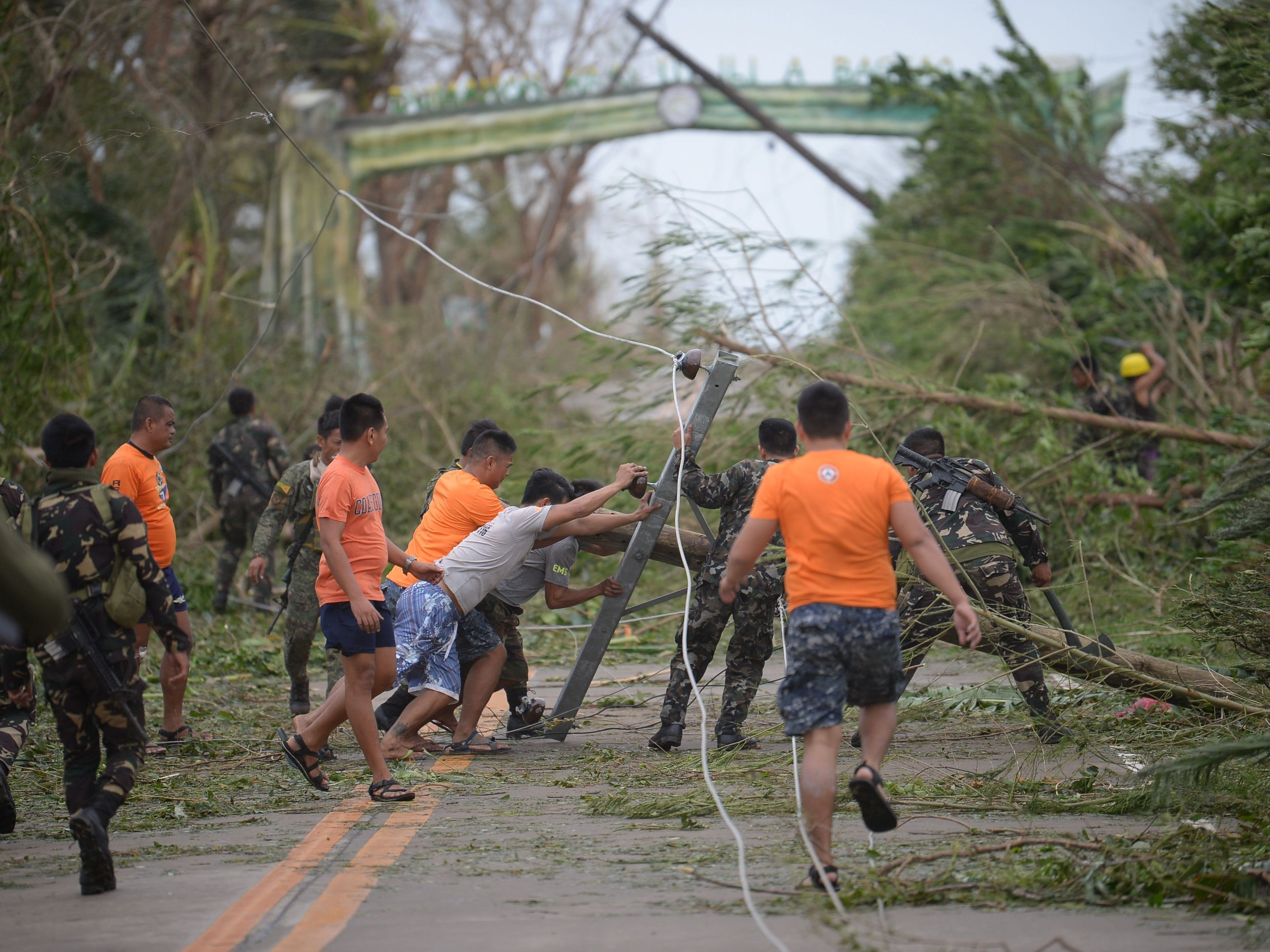 Rescue workers clear a road of debris and toppled electric posts caused by strong winds due to super Typhoon Mangkhut as they try to reach Baggao in Cagayan province, north of Manila Sept. 15, 2018.