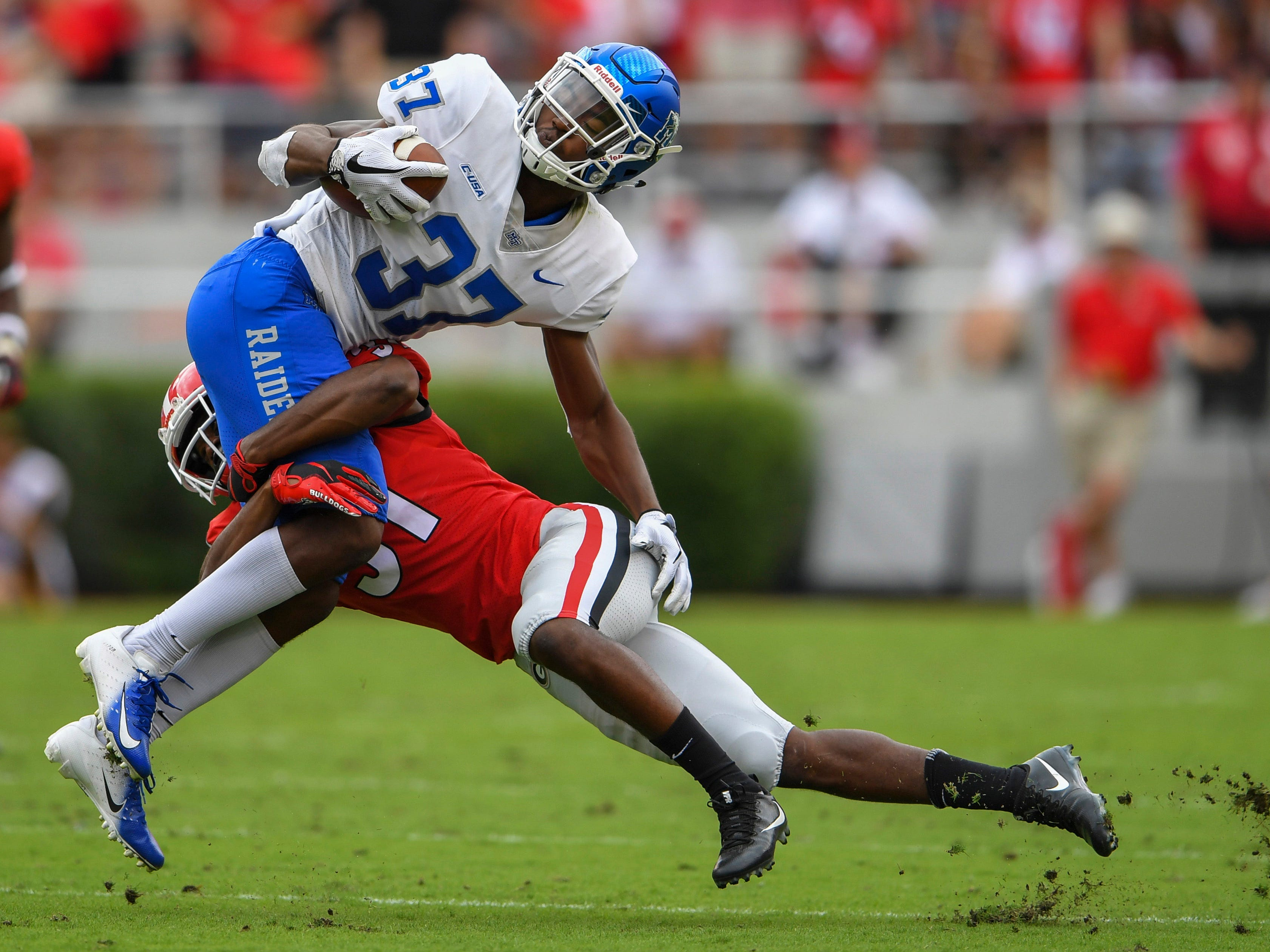 Georgia Bulldogs defensive back William Poole (31) hits Middle Tennessee Blue Raiders wide receiver Patrick Smith (37) during the first half at Sanford Stadium.