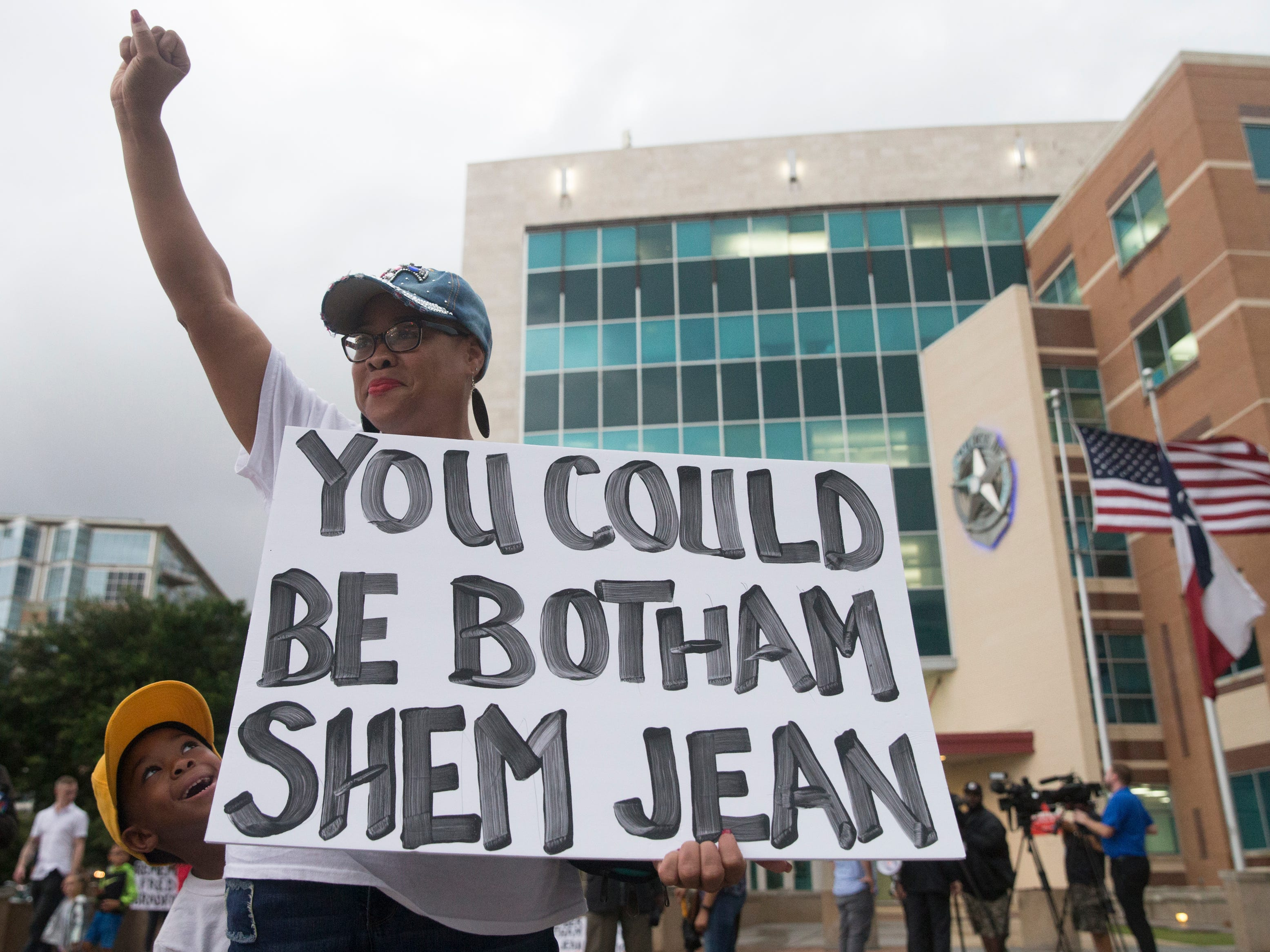 "Dr. Pamela Grayson raises her fist as ""Young King"" Solomon Grayson, 6, peaks behind her sign during a Mothers Against Police Brutality candlelight vigil for Botham Jean at the Jack Evans Police Headquarters on Friday, Sept. 7, 2018, in Dallas."