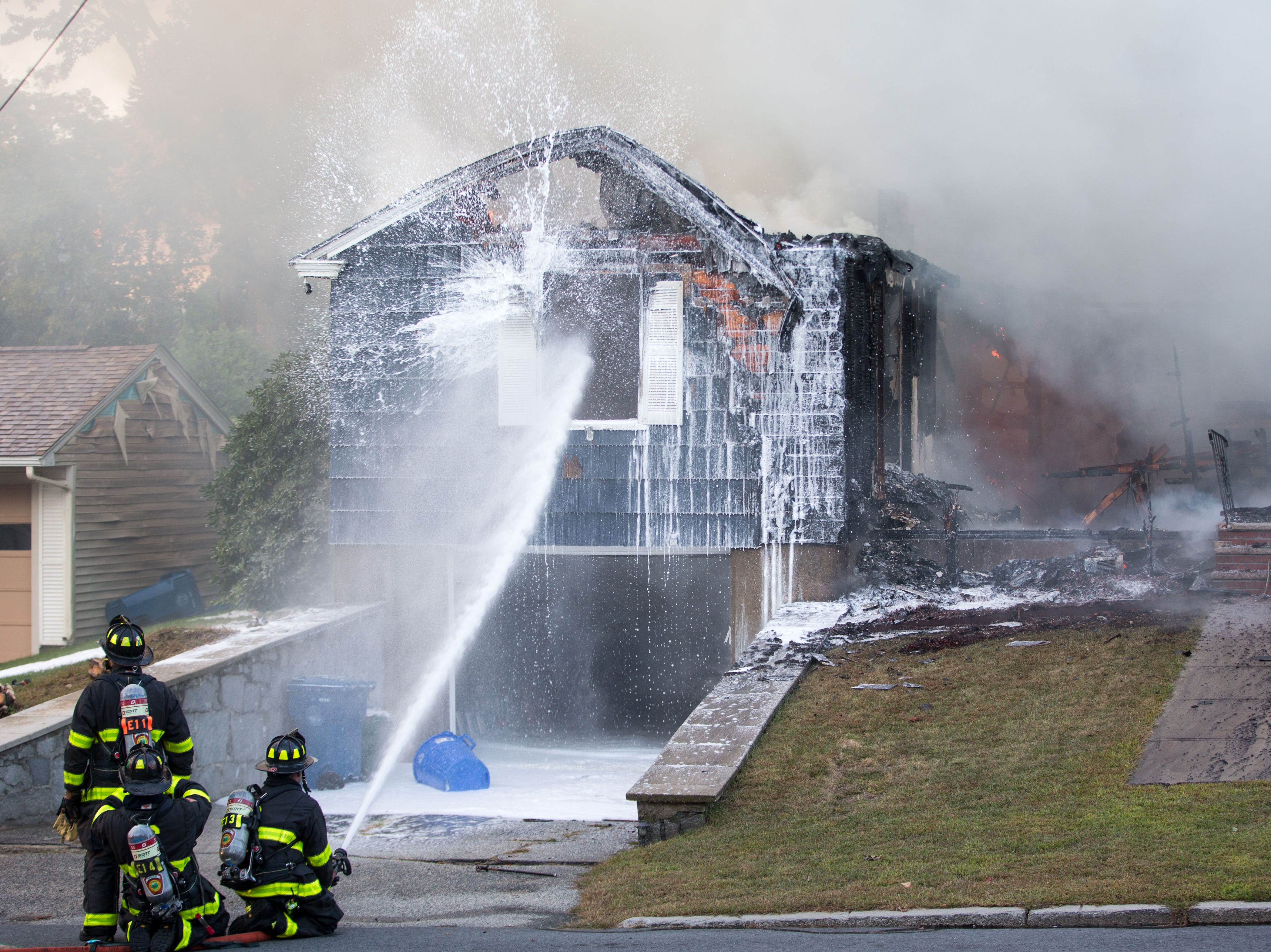 Firefighters work to extinguish a fire caused by over pressurized gas lines on Sept. 13, 2018, in Lawrence, Mass. Dozens of fires broke out in Lawrence, North Andover and Andover because of the gas lines.
