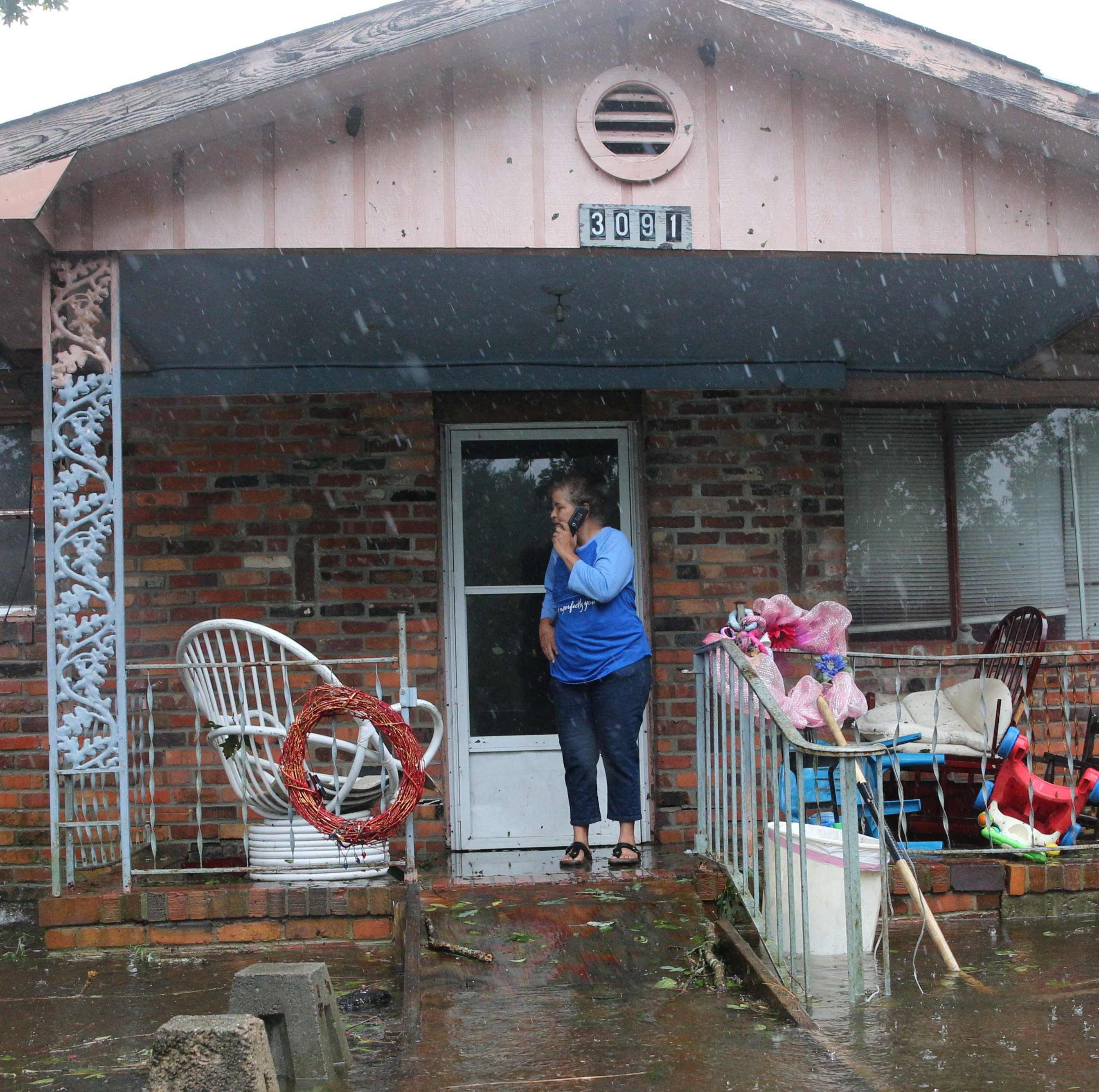 A woman on a cellphone calls for help at her flooded residence in Lumberton, N.C., on Sept. 15, 2018, after Tropical Storm Florence dumped relentless rain in the state. Members of the Cajun Navy came to her rescue.