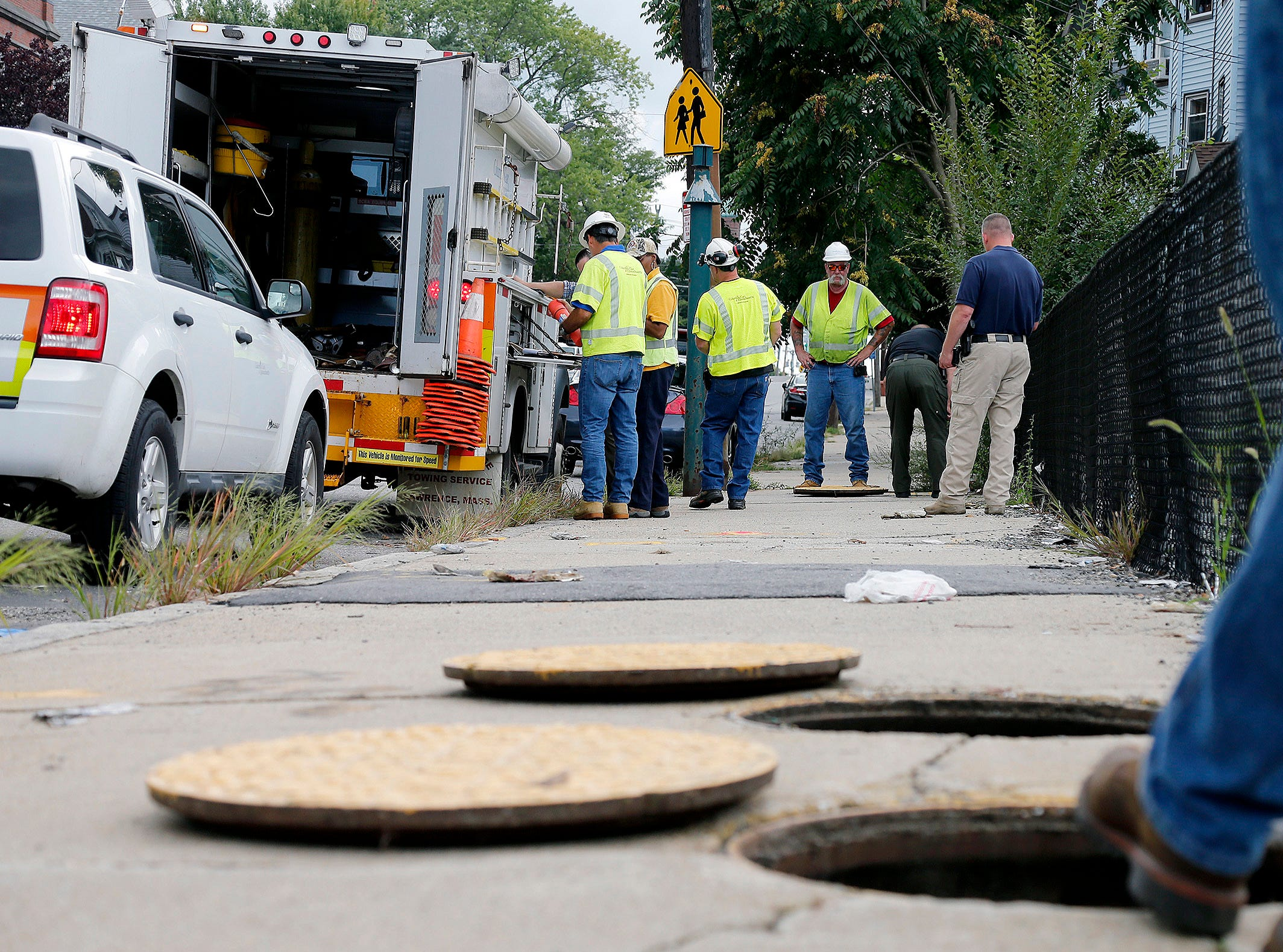 A worker with Columbia gas stands over an open man hole as the crew works to make sure there are no gas leaks at the corner of Parker and Salem Streets in Lawrence, Mass., Friday. Multiple houses were damaged Thursday afternoon from gas explosions and fires triggered by a problem with a gas line that feeds homes.