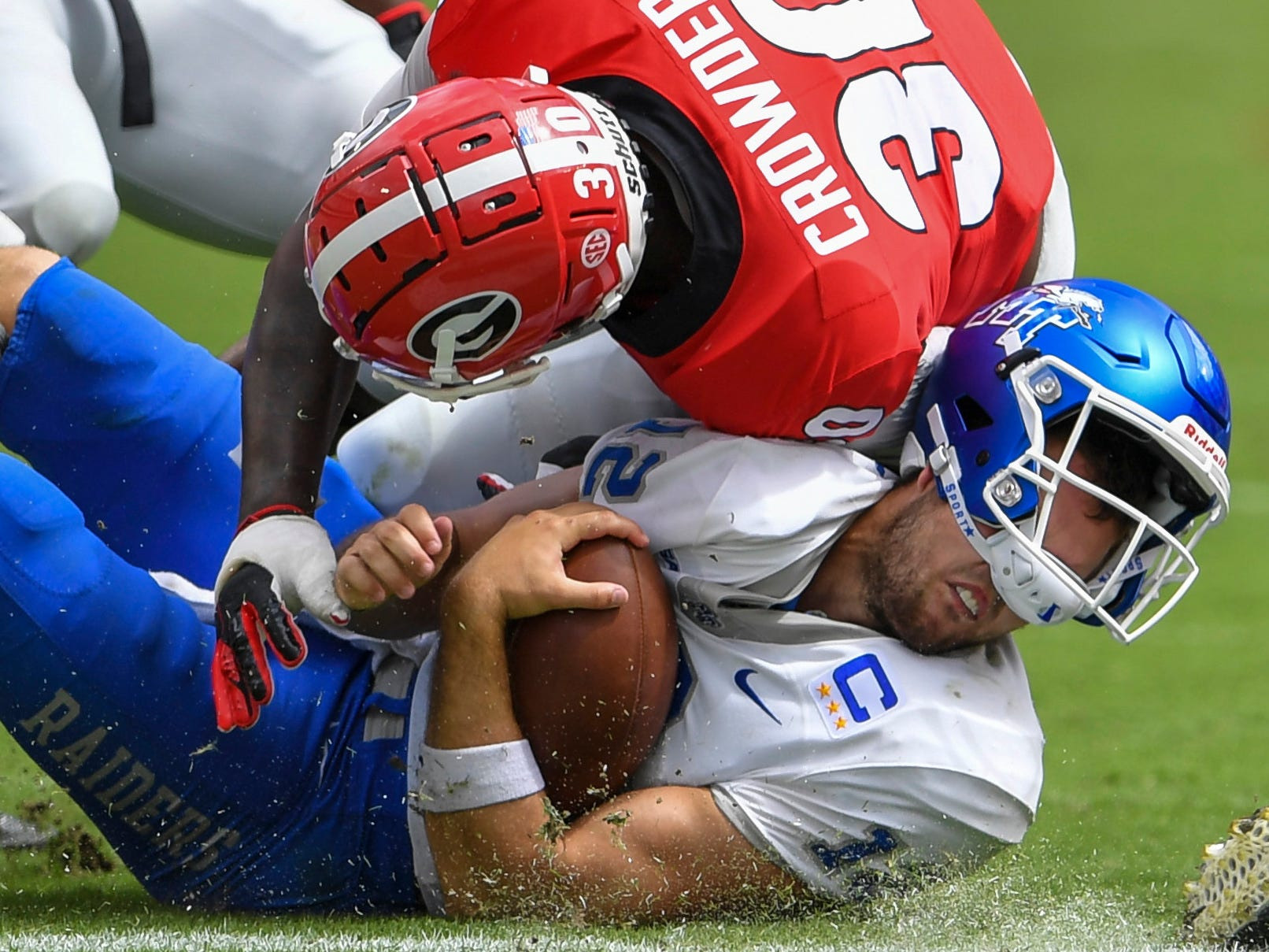 Georgia Bulldogs linebacker Tae Crowder (30) tackles Middle Tennessee Blue Raiders quarterback Brent Stockstill (12) during the second half at Sanford Stadium.