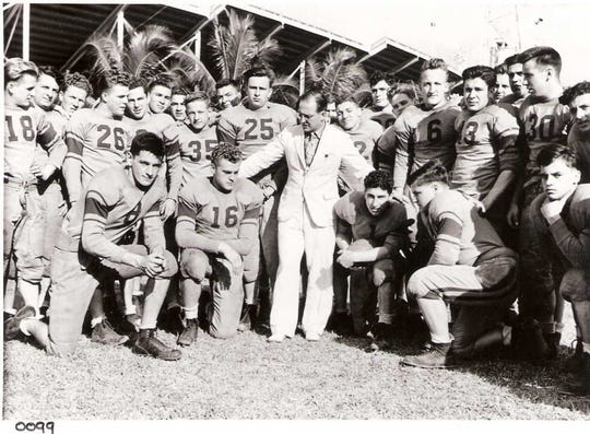 The 1939 Garfield High School football team gather around coach Art Argauer outside the Orange Bowl before  playing for a national championship against Miami High School.