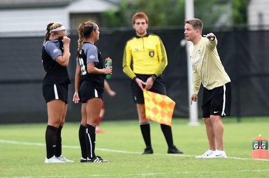 Hardin-Simmons coach Marcus Wood talks with Randie Dennison (10) and Ellie Ratliff (7) during the Cowgirls' 3-1 win against Sul Ross State on Saturday, Sept. 15, 2018. It was the first night game with lights at the HSU Soccer Complex.