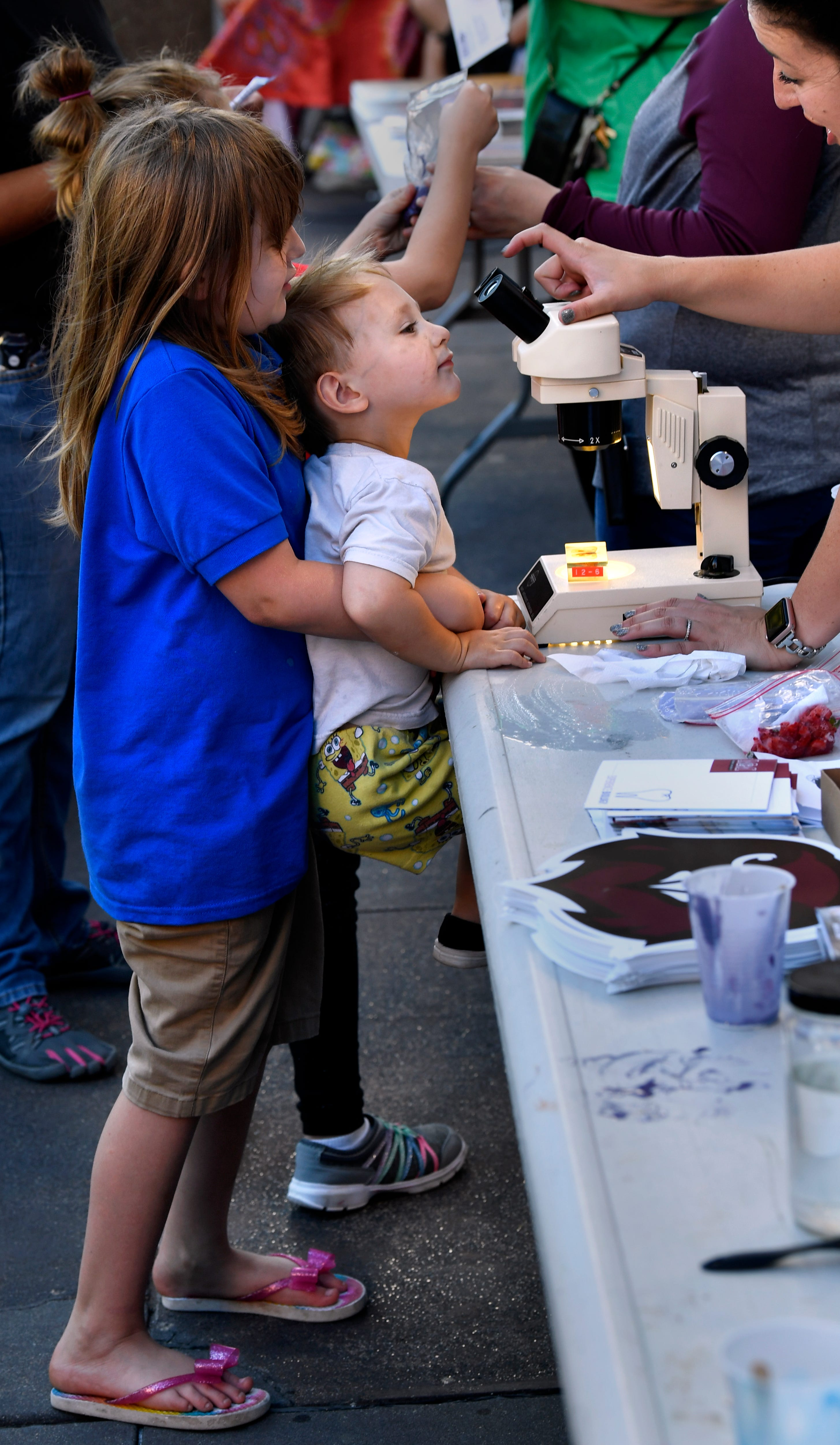 Aeris Moss, 6, lifts her two-year-old brother Eden up to a microscope Thursday during ArtWalk in downtown Abilene. ArtWalk's theme this month was STEAMpunk, celebrating Science, Technology, Engineering, Art and Mathematics.