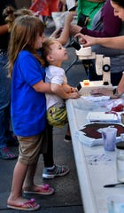 Aeris Moss, 6, lifts her two-year-old brother Eden up to a microscope Thursday Sept. 13, 2018 during ArtWalk in downtown Abilene. ArtWalk's theme this month was STEAMpunk, celebrating Science, Technology, Engineering, Art and Mathematics. Steampunk is also a fictional genre that mixes technology with a 19th Century aesthetic.